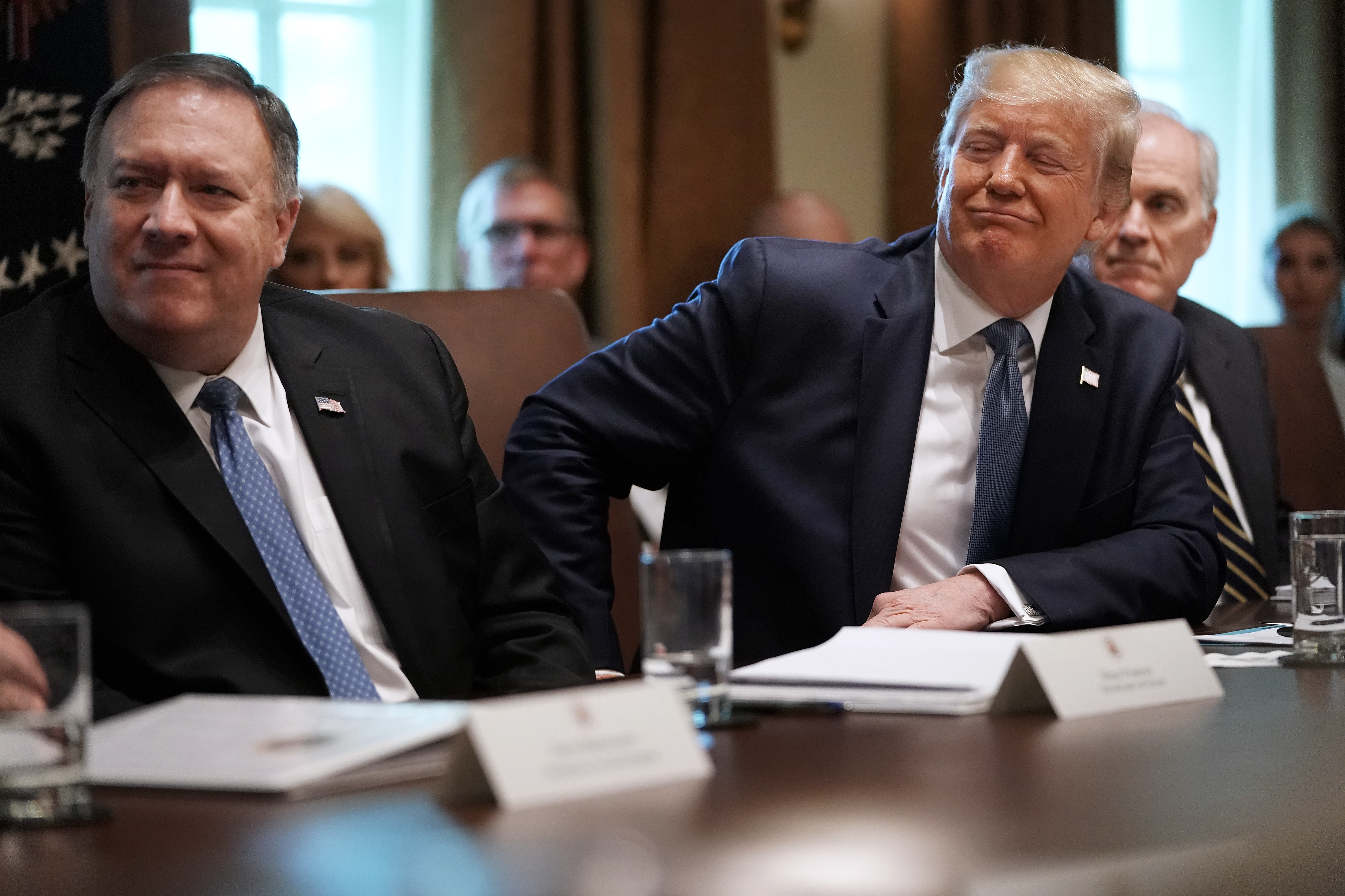 Trump and Secretary of State Mike Pompeo listen during a July 2019 cabinet meeting.