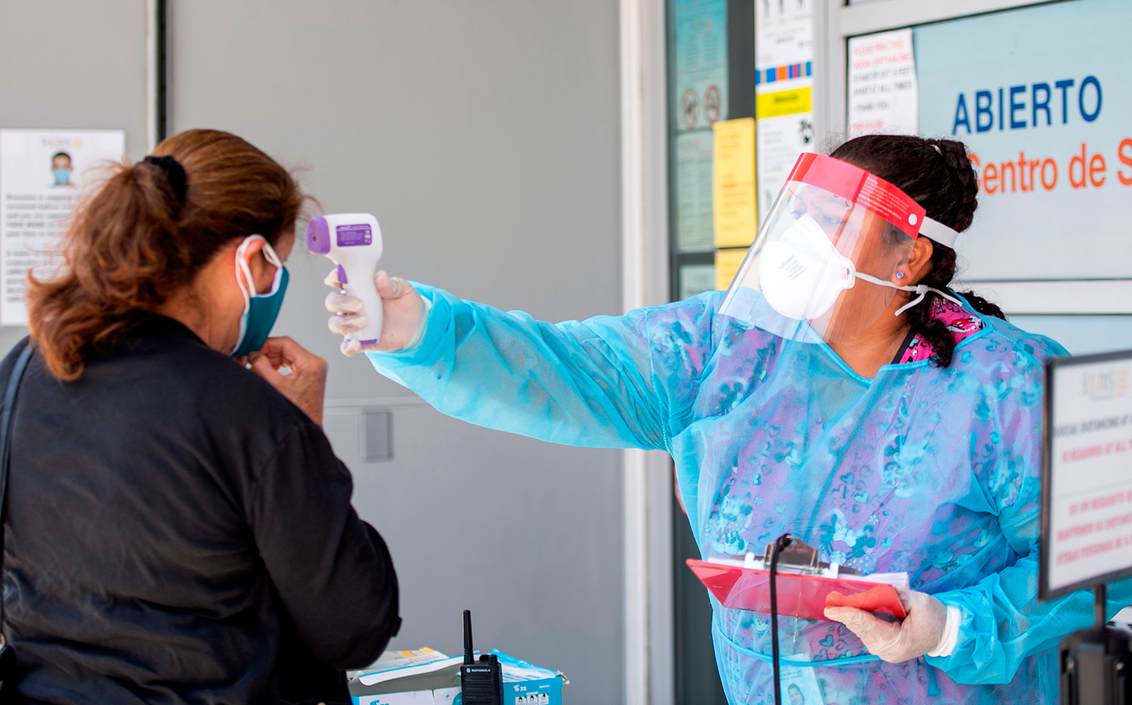 A health worker takes a patient's temperature before sending them to a tent to be tested at a Covid-19 testing site in Los Angeles on July 24.