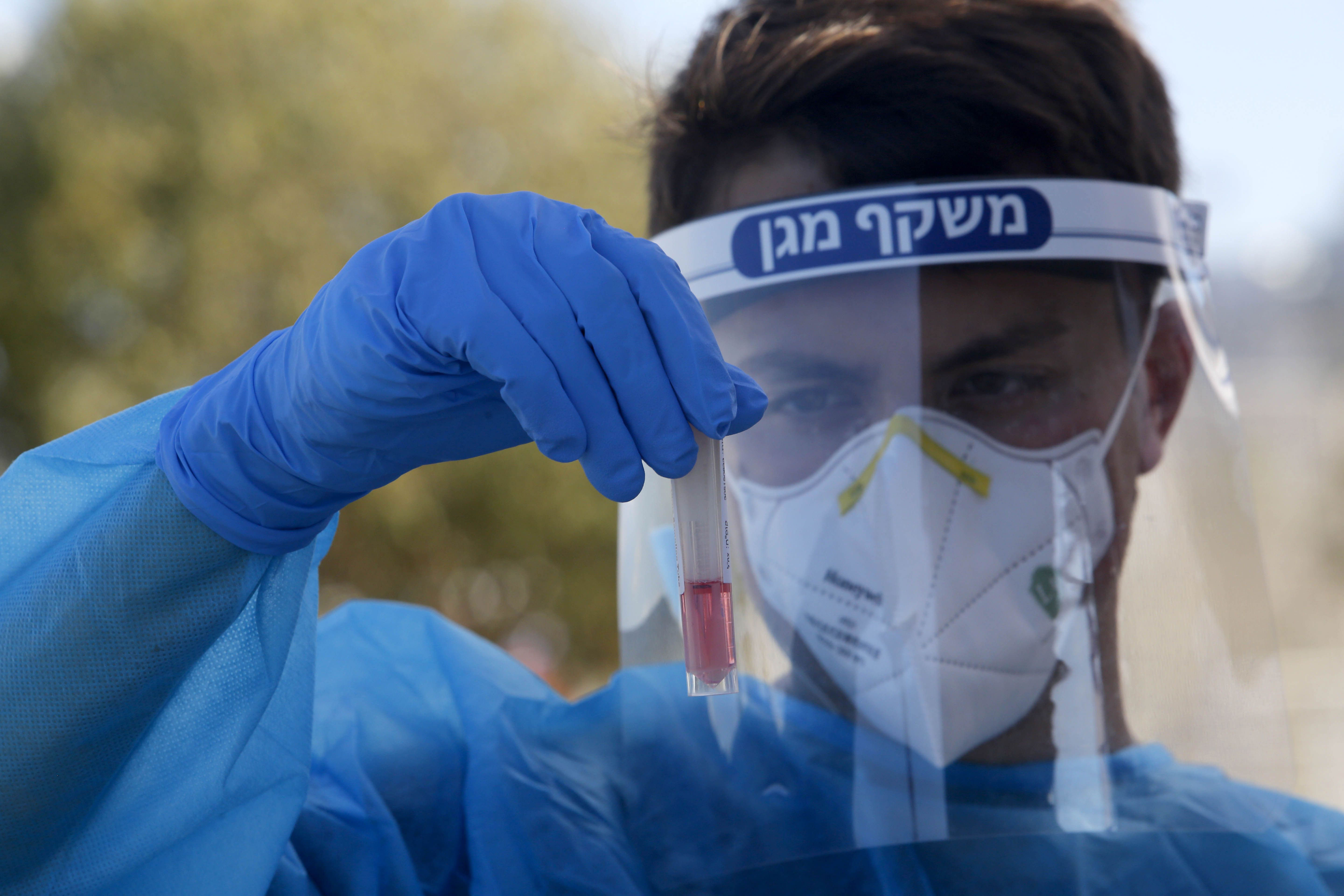 A medical worker holds a Covid-19 test sample in Petah Tikva, Israel, in October 2020.