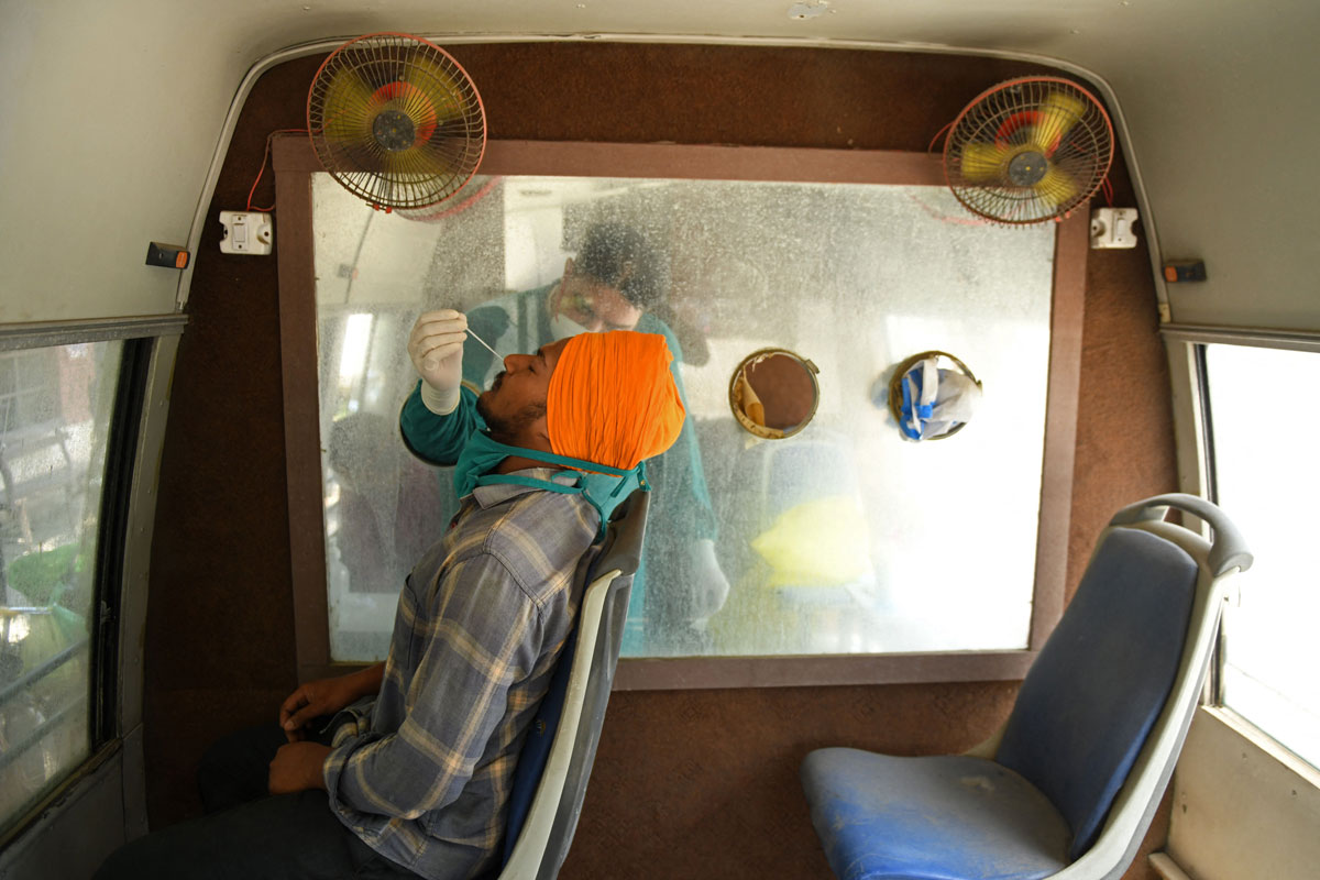 A health worker collects a nasal swab samplein a mobile testing van in Amritsar, India on May 24.