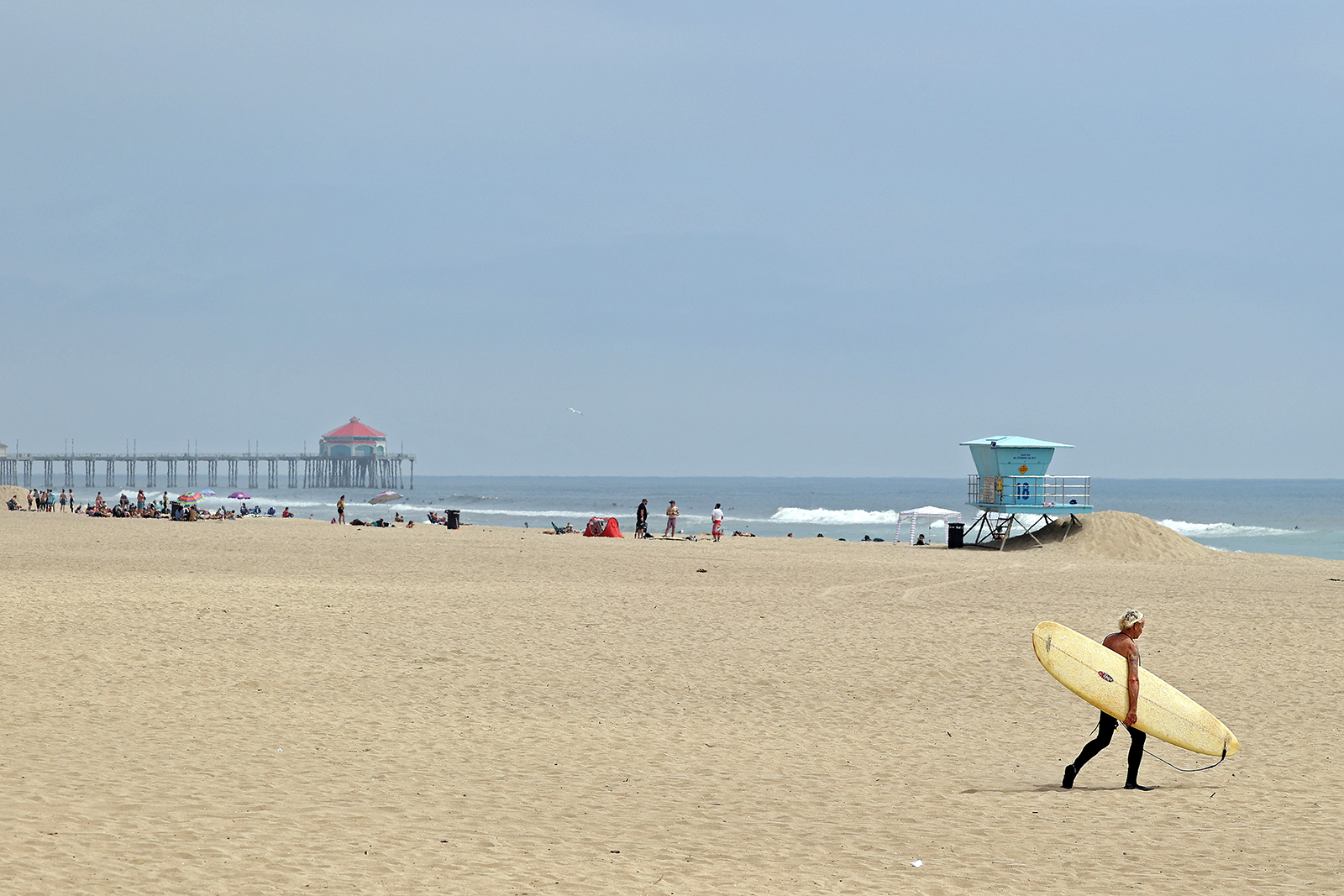 A surfer walks on the beach in front of the pier on April 30, in Huntington Beach, California.