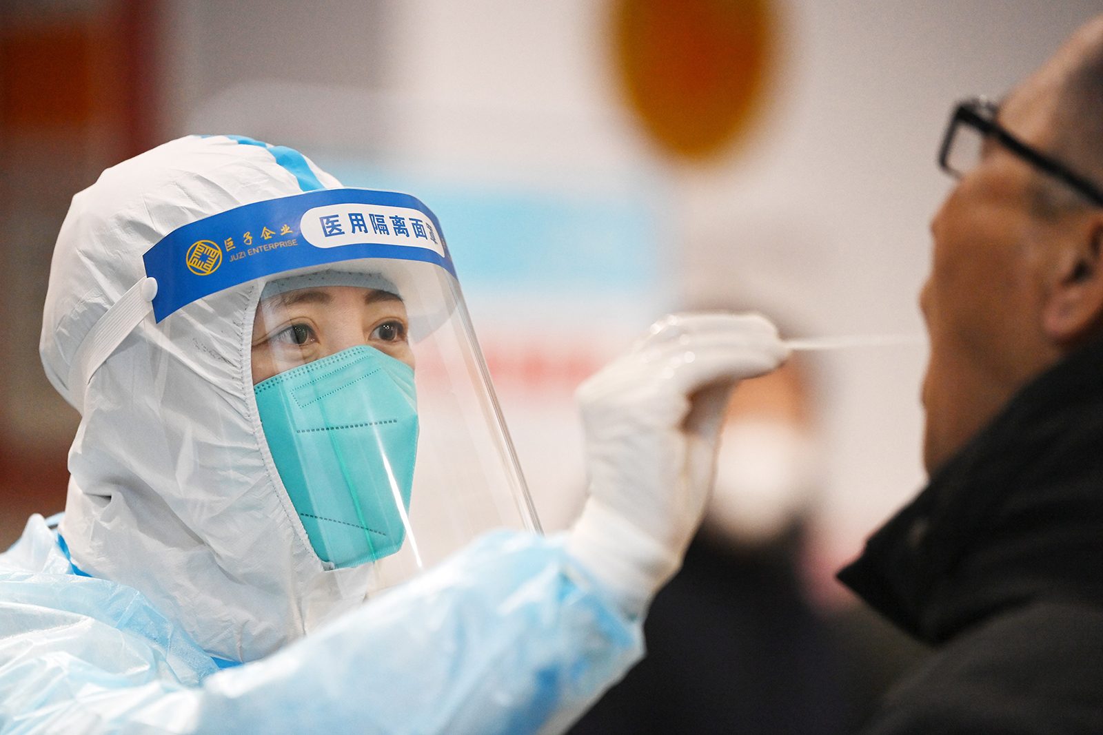 A medical worker collects a nucleic acid sample at a testing site in Harbin, northeast China's Heilongjiang Province, on January 23.
