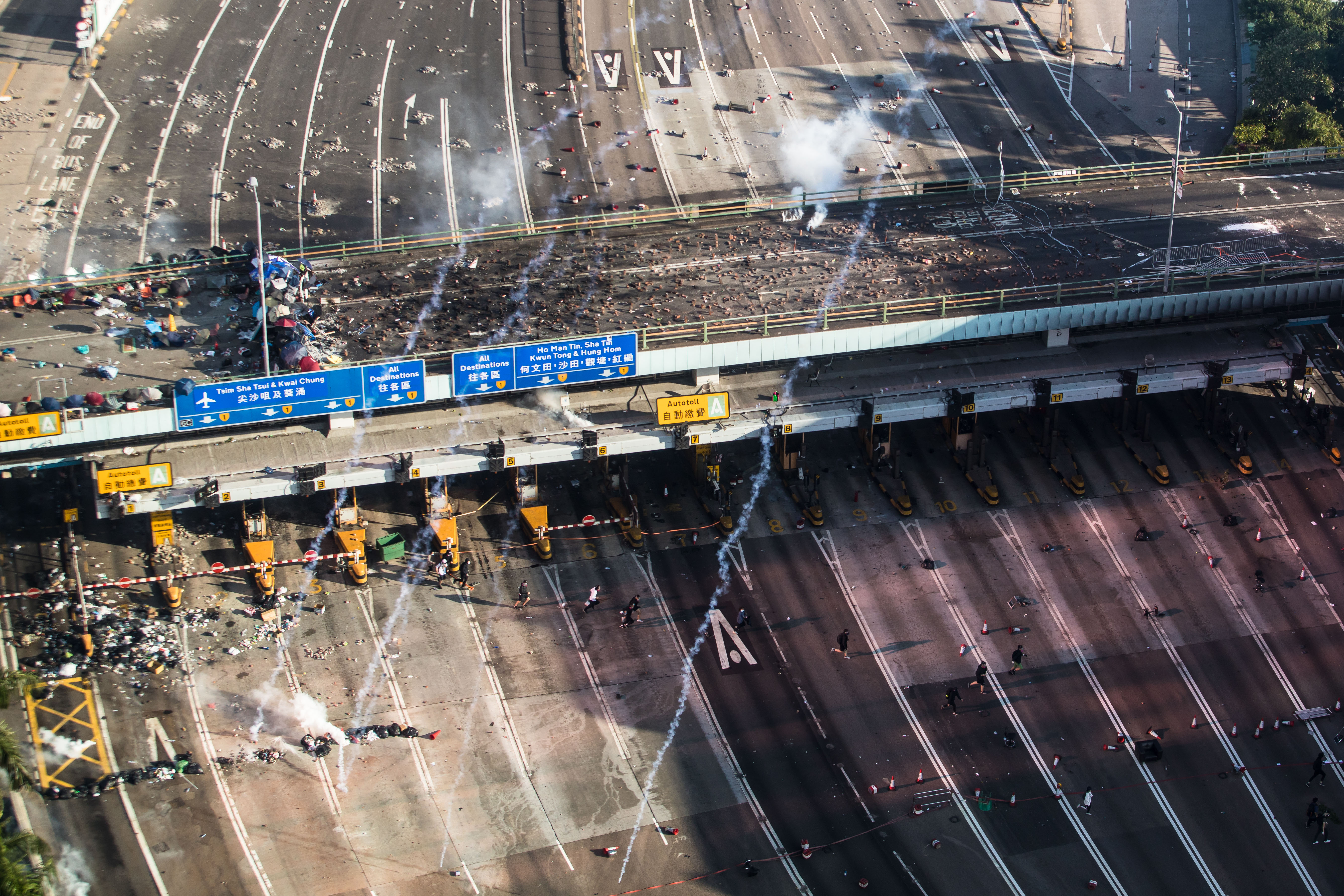 Police fire tear gas as protesters run on a road leading to the Cross Harbour Tunnel while trying to leave Hong Kong Polytechnic University in Hung Hom district of Hong Kong on November 18.