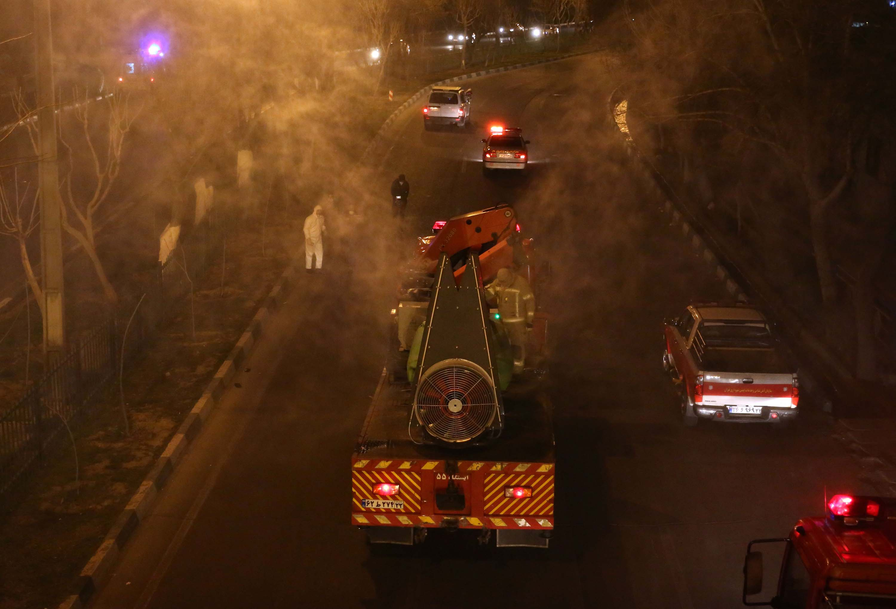 Iranian firefighters disinfect streets in Tehran, Iran, on Wednesday.