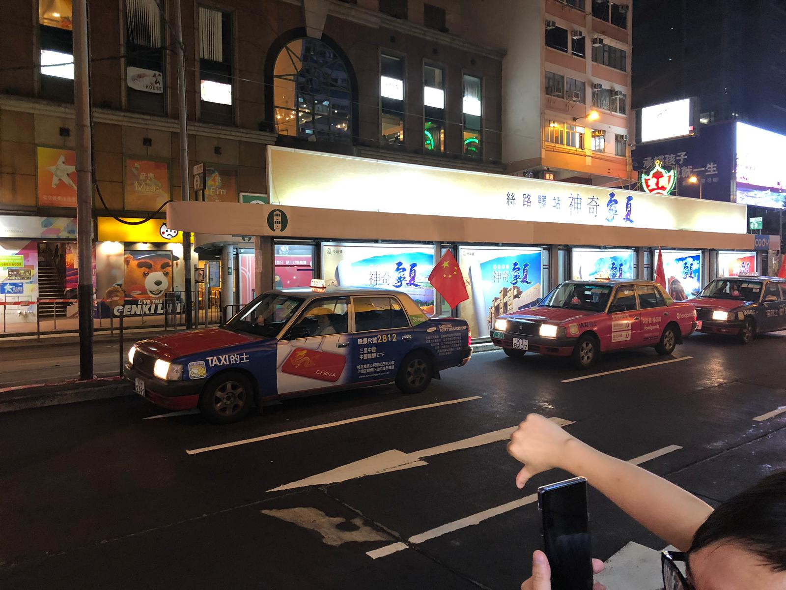 People yell at a taxi showing a Chinese flag.