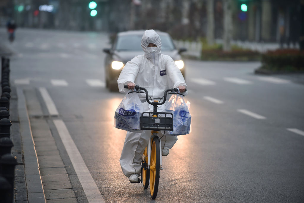A resident wears a protective suit as they ride a bicycle in Wuhan in China's central Hubei province on February 27, 2020.