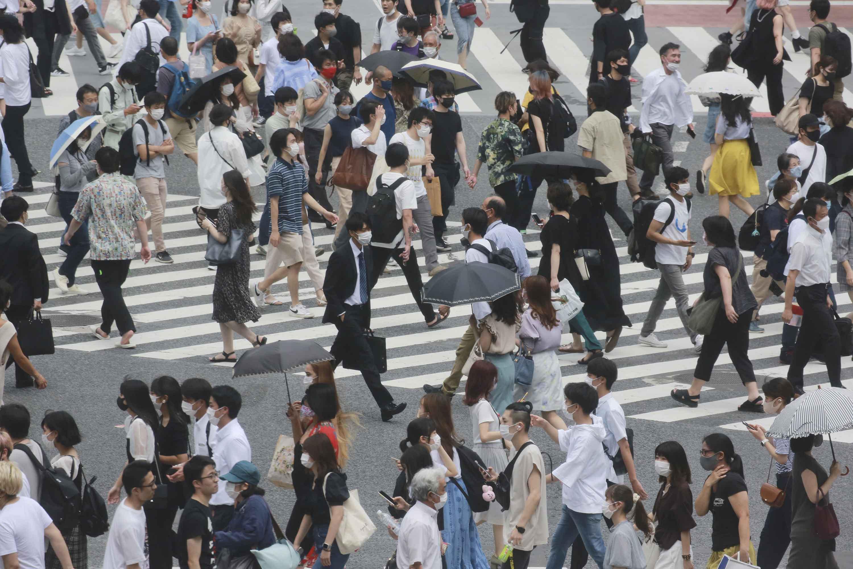 People cross a street in Tokyo on Wednesday, July 28.