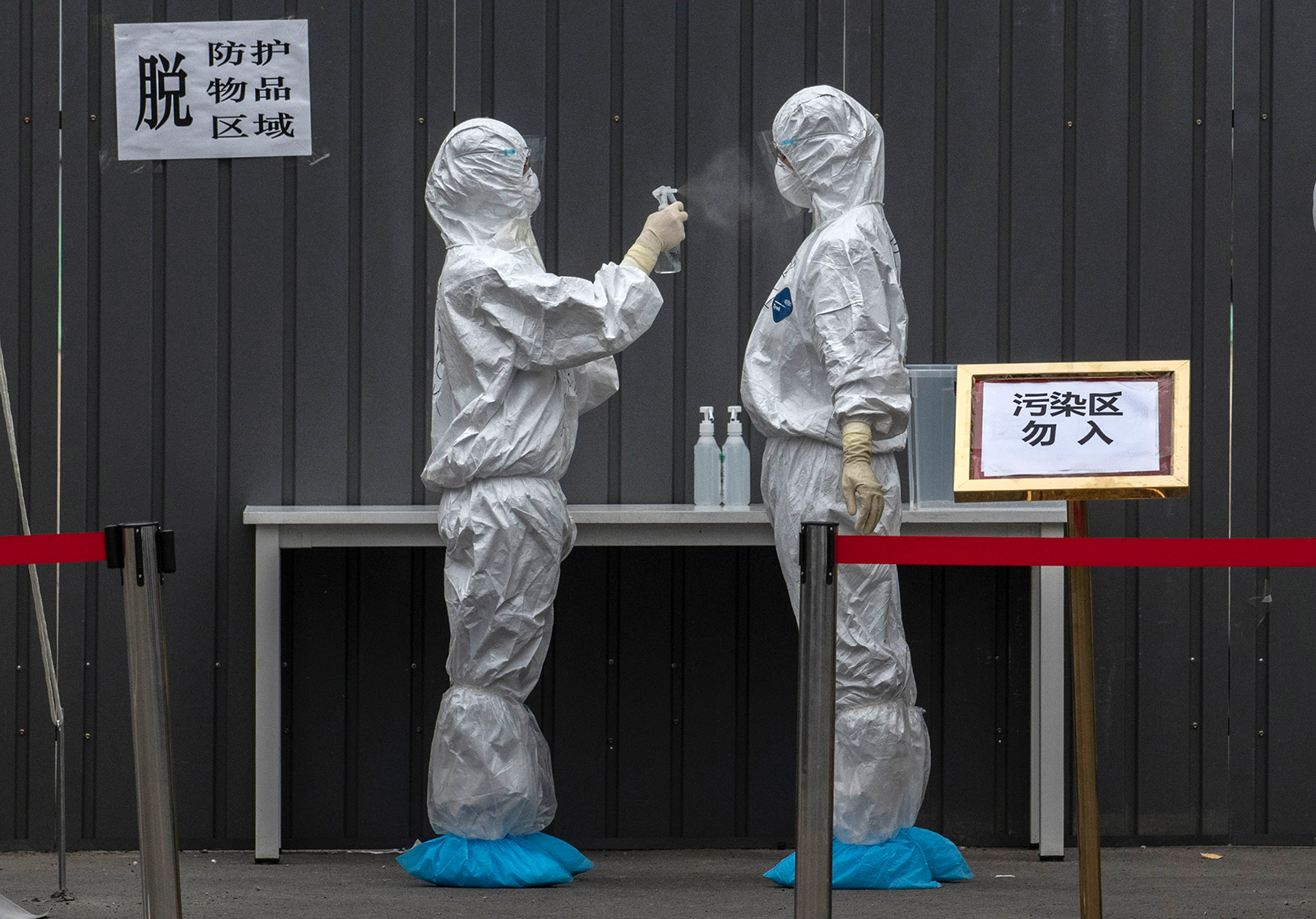 Chinese epidemic control workers wear protective suits as they disinfect each other after performing nucleic acid swab tests for Covid-19 on citizens at a government testing site in Xicheng District on June 24 in Beijing.