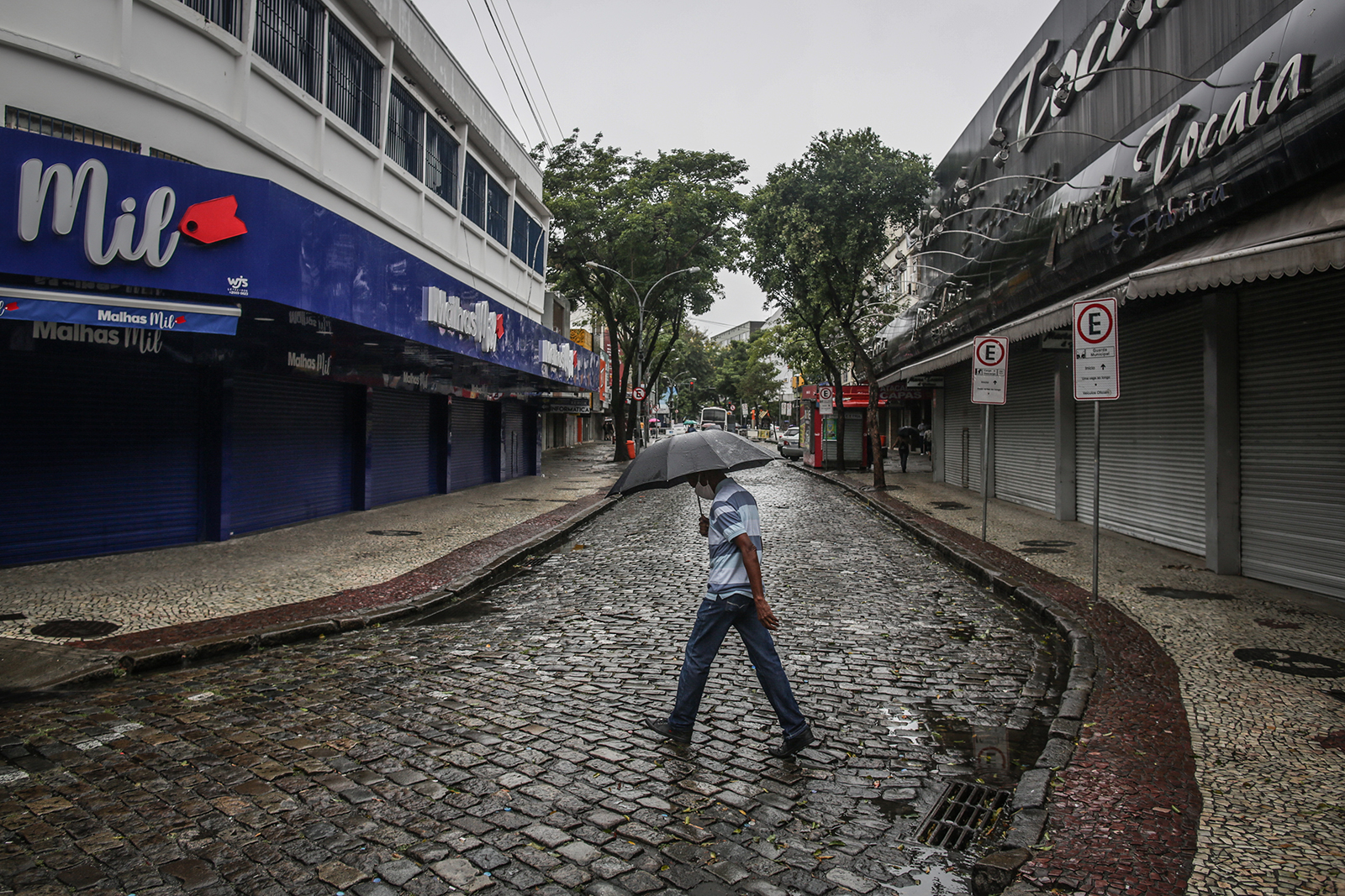 A pedestrian wearing a protective mask holds an umbrella while passing in front of businesses temporarily closed in the Campo Grande neighborhood of Rio de Janeiro, Brazil, on May 7.
