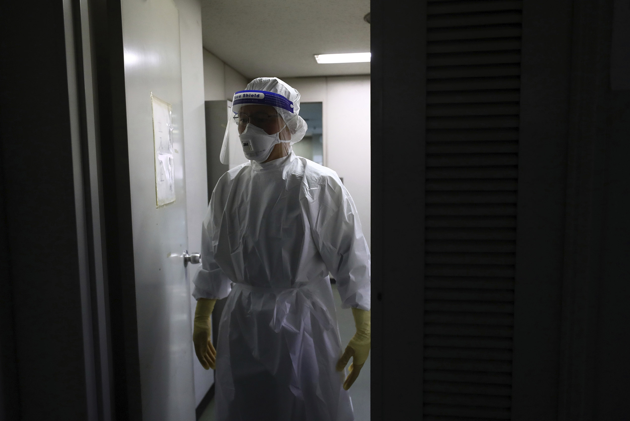 A doctor wearing personal protective equipment, conducts a polymerase chain reaction (PCR) test in the Setagaya Ward, Tokyo, Japan, on July 18.