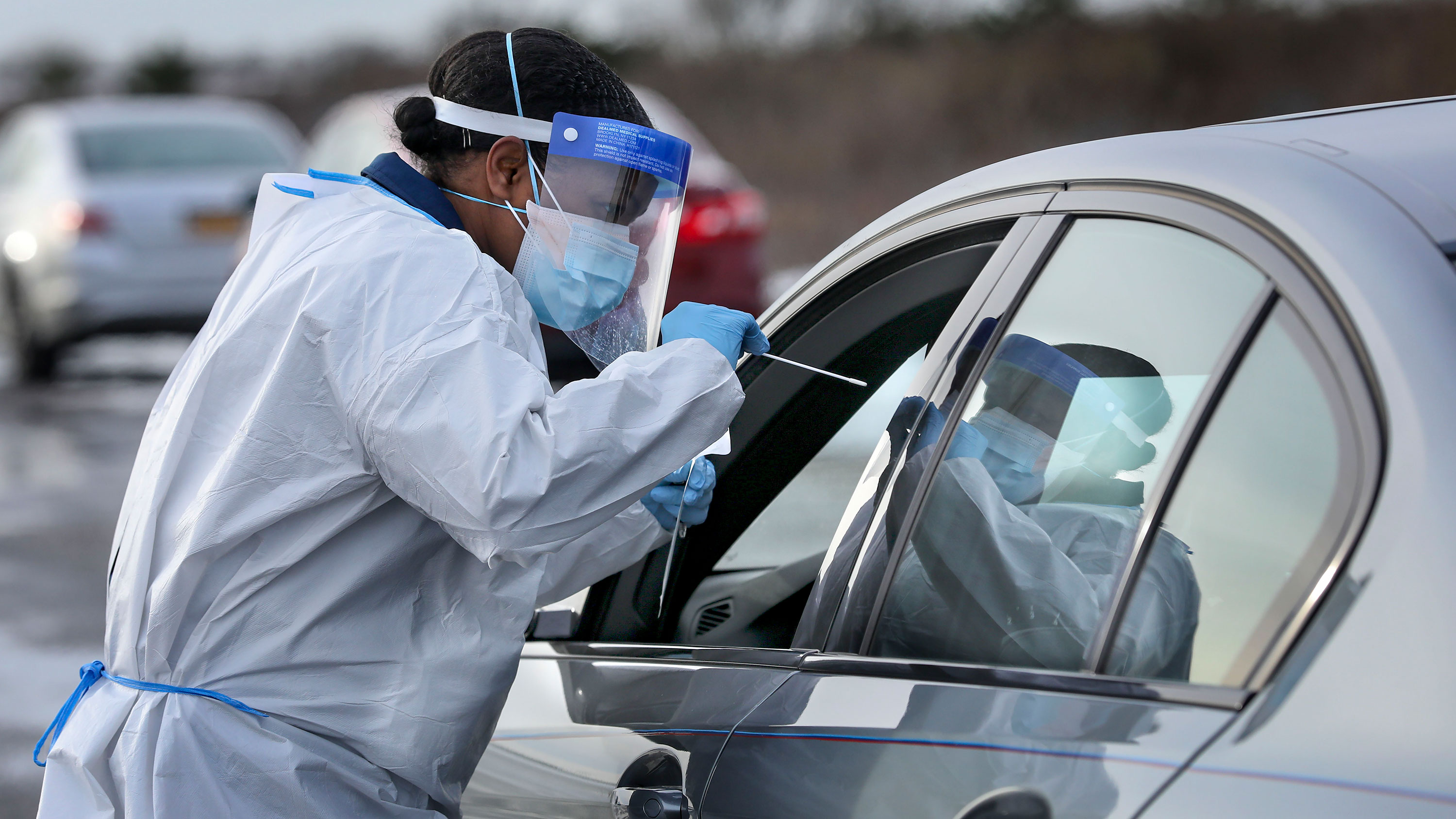 A nurse administers a Covid-19 swab test at a drive-thru testing site in Shirley, New York, on December 19.