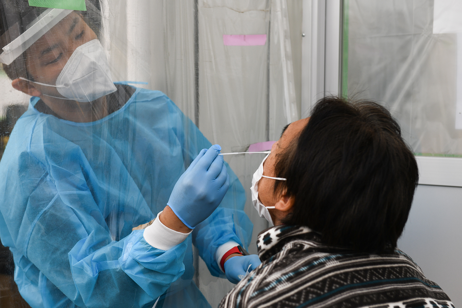 A healthcare worker wearing personal protective equipment (PPE) collects a swab sample at the coronavirus testing center set up at Fujimino Emergency Hospital in Miyoshi-machi, Saitama Prefecture, Japan, on December 9.