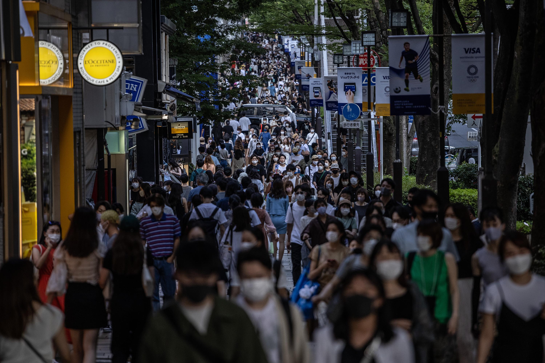 People walk along a crowded shopping street in Tokyo, Japan, on July 24.