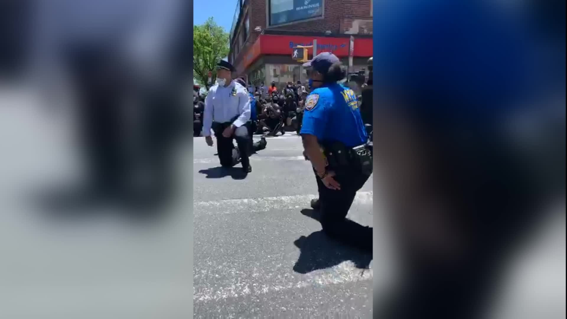 NYPD officers are seen kneeling with protesters on May 31.