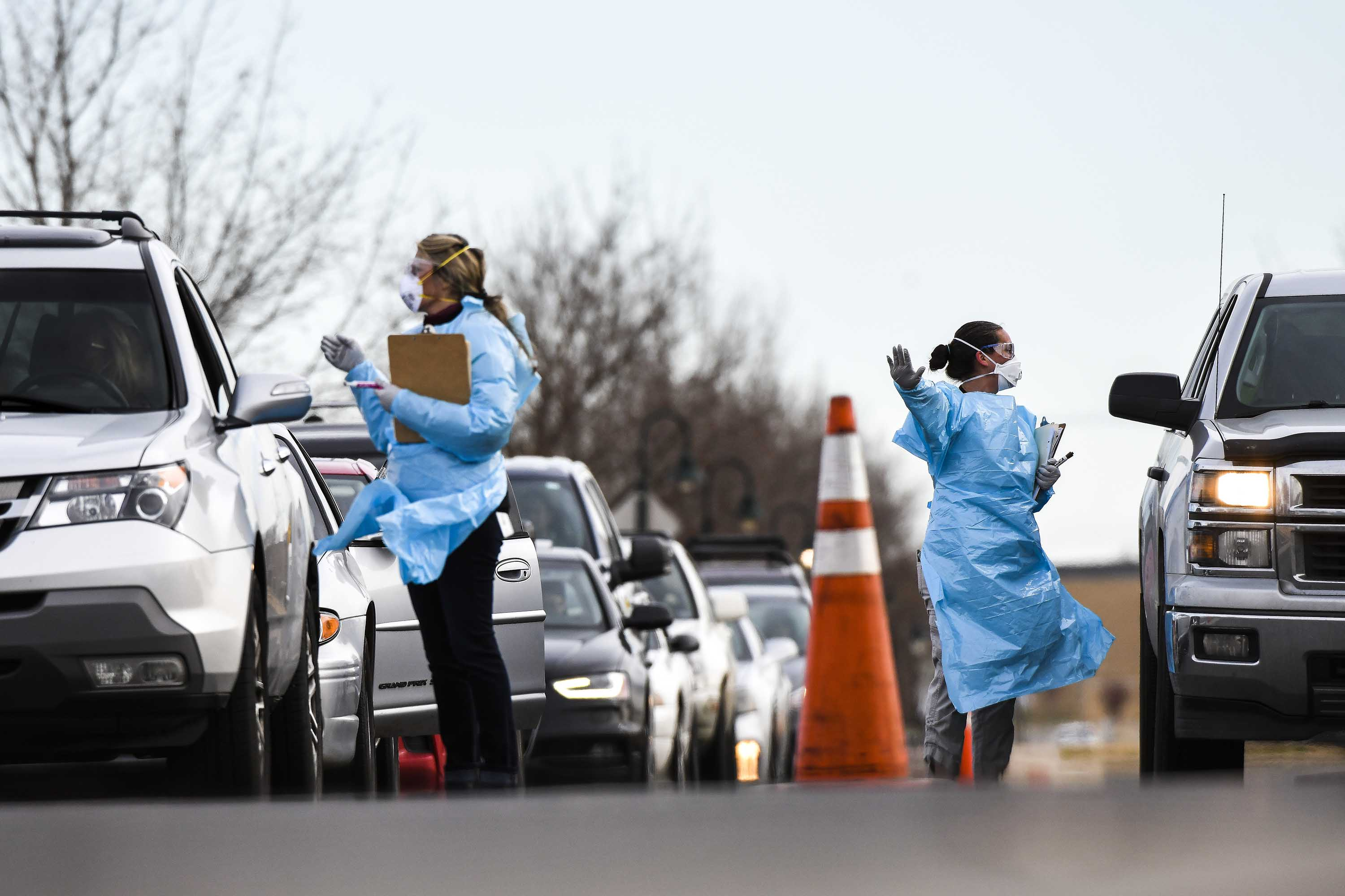 Workers from the Colorado Department of Public Health and Environment check in with people waiting to be tested for coronavirus at the state's first drive-up testing center in Denver, Colorado, on Thursday.