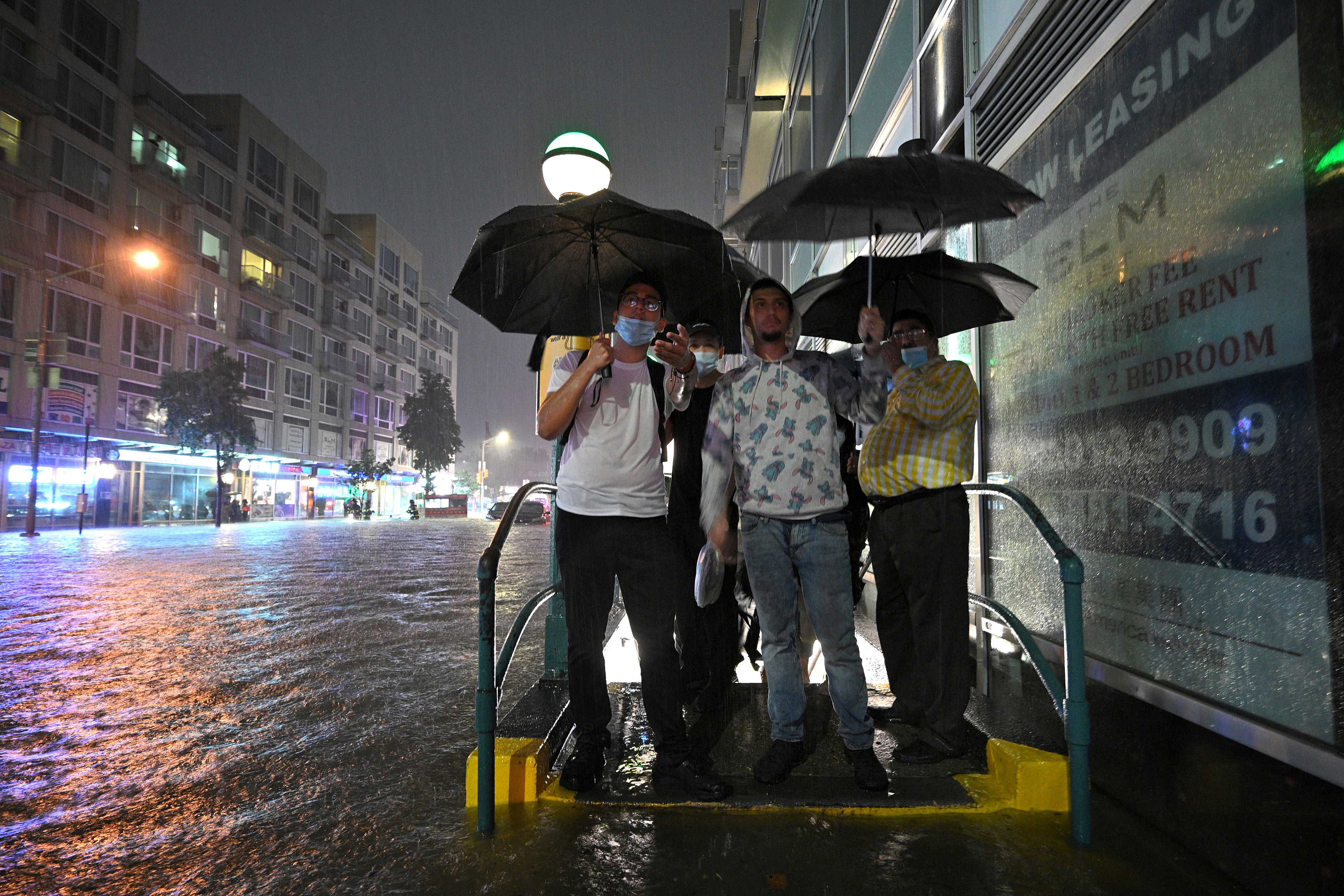 People stand at a flooded subway entrance as they debate wading through high water caused by the remnants of Hurricane Ida, in Queens, New York, on September 1.