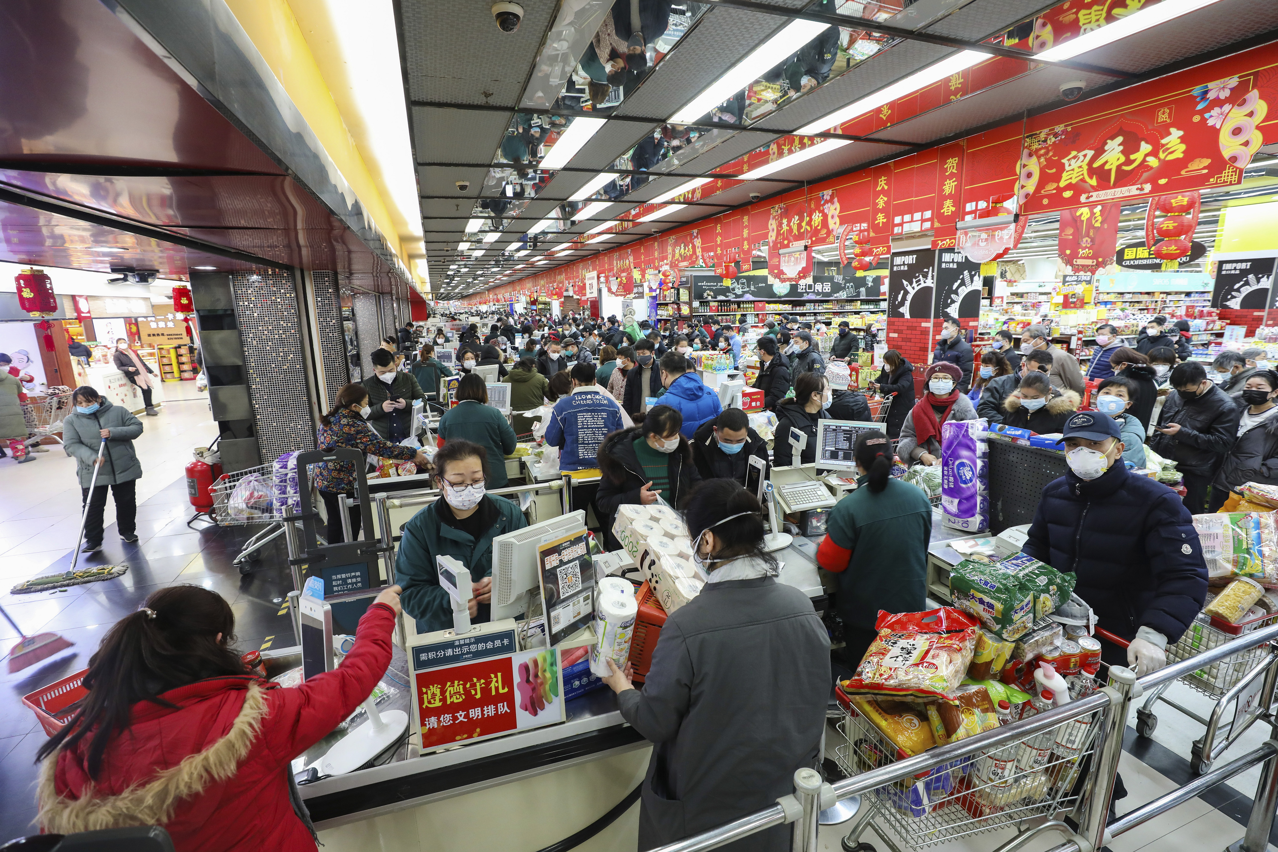 Shoppers wearing face masks pay for their groceries at a supermarket in Wuhan on Saturday.
