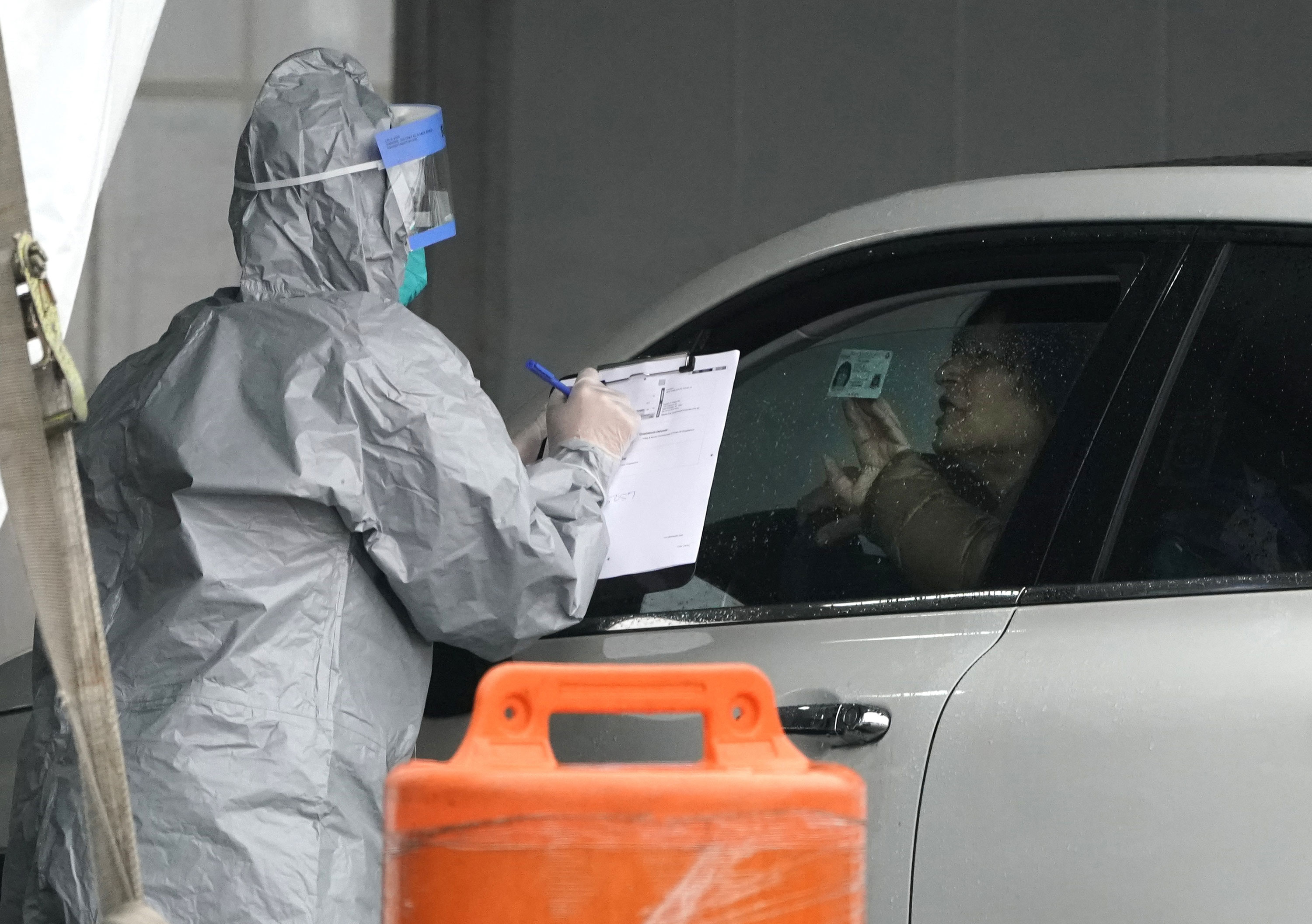 A worker in protective suits checks the identification of a patient as people arrive by car to be tested for Coronavirus at the state's first drive-through testing center in New Rochelle, New York,on March 13.