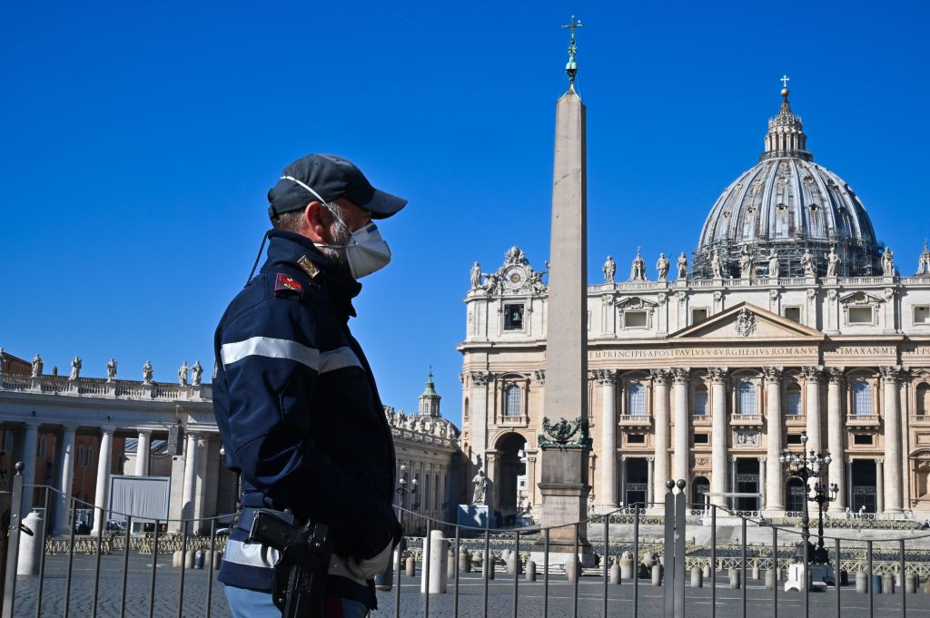 Un ofițer de poliție care poartă o mască de protecție stă de pază în Piața Sf. Petru din Vatican și în bazilica sa principală pe 11 martie, la o zi după ce au fost închise turiștilor ca parte a unei represiuni mai largi pentru combaterea coronavirusului .