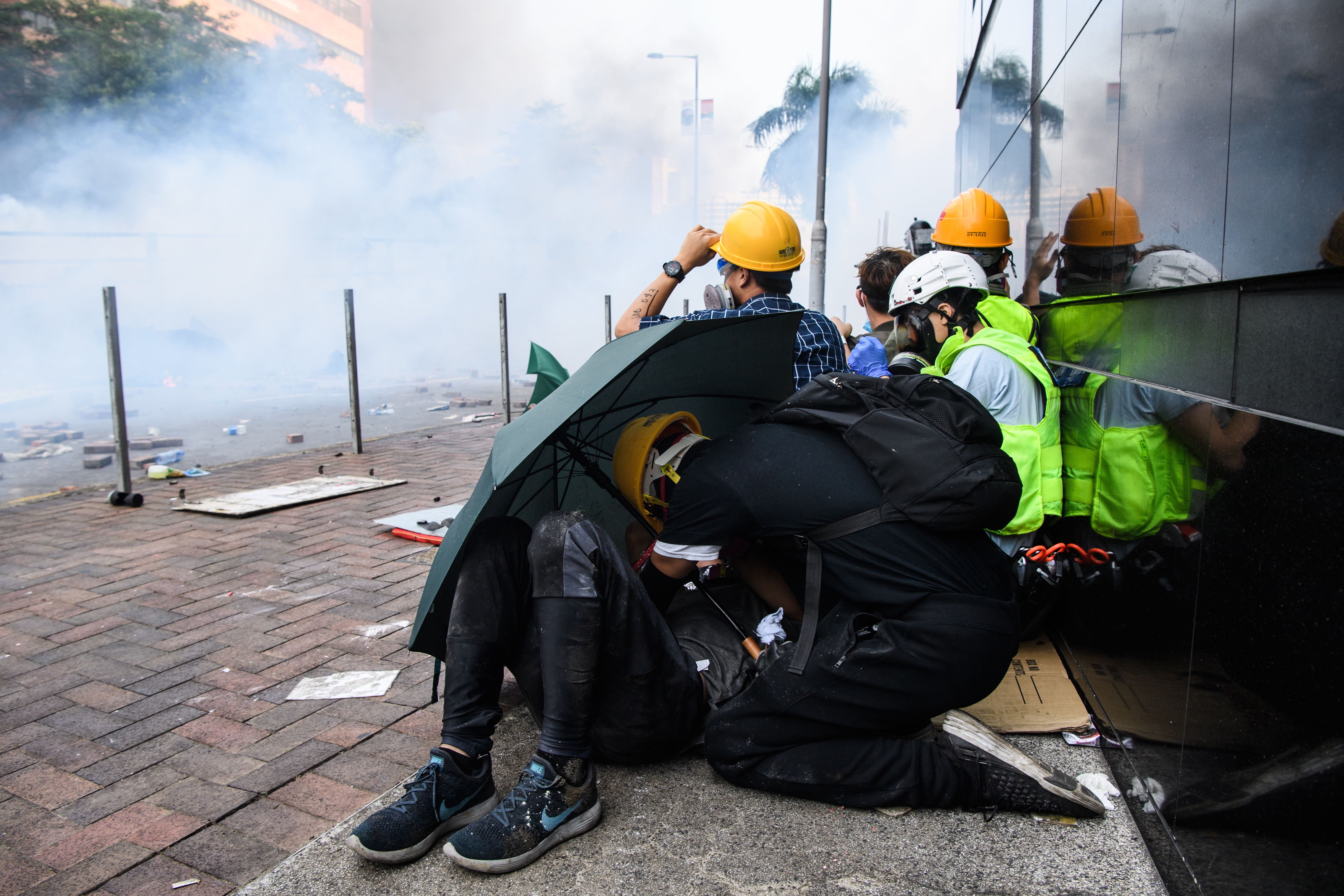 Protesters huddle as police fire tear gas in Hong Kong Polytechnic University on November 18, 2019.