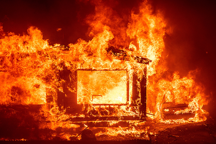 A mobile home and car burn at Spanish Flat Mobile Villa as the LNU Lightning Complex fires tear through unincorporated Napa County, Calif., on Tuesday, Aug. 18, 2020.