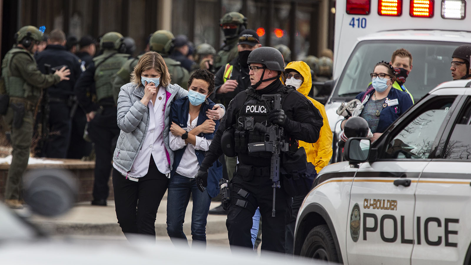 Healthcare workers walk out of a King Sooper's Grocery store after a gunman opened fire on March 22, in Boulder, Colorado.