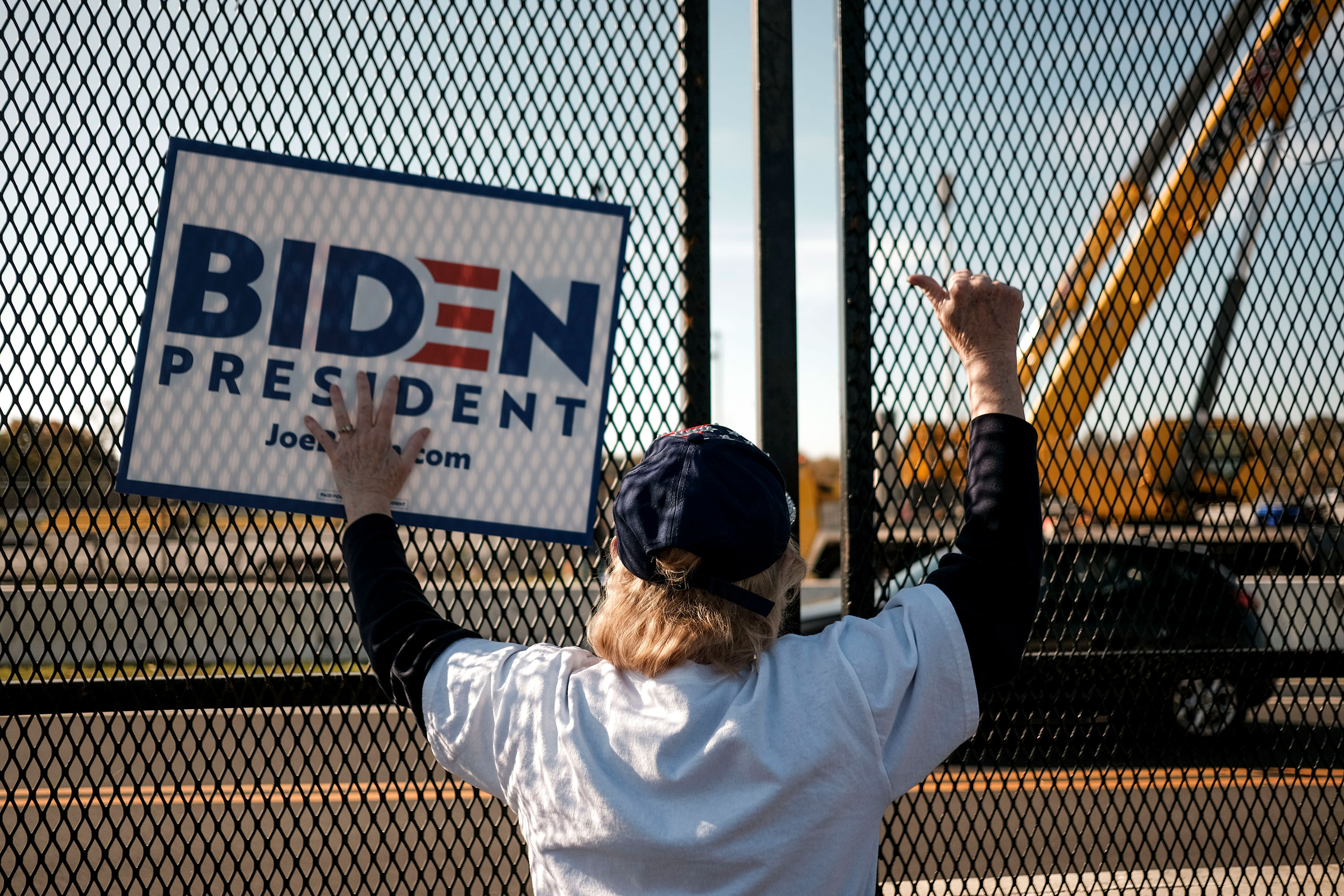 A Joe Biden supporter waits outside the Chase Center in Wilmington, Delaware, on November 7, 2020.
