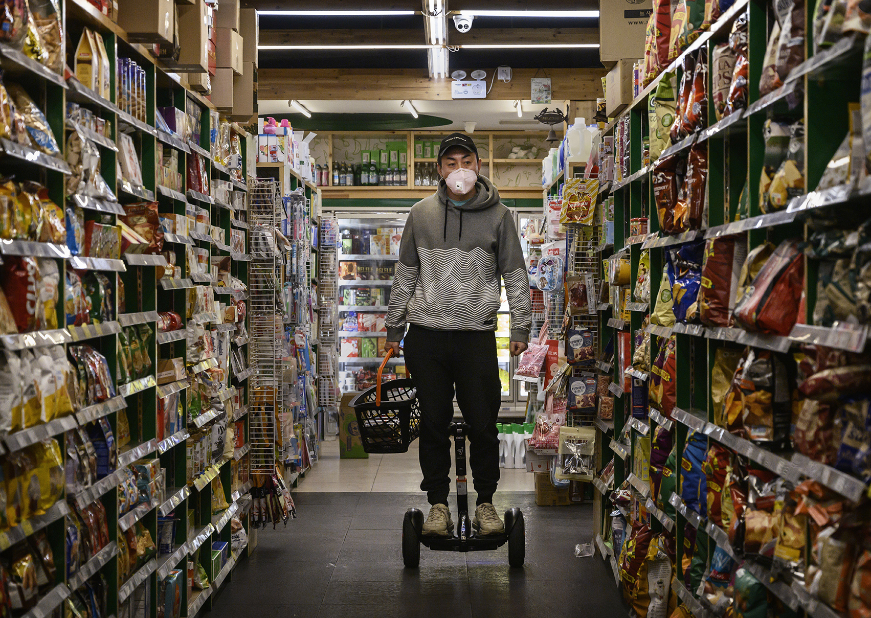 A man wears a protective mask as he rides a segway in a grocery store while shopping on February 11 in Beijing.