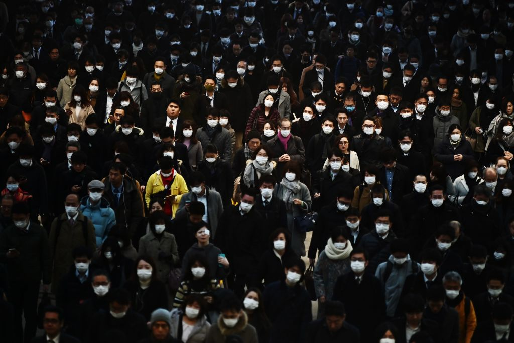 Mask-clad commuters make their way to work during morning rush hour in Tokyo today.