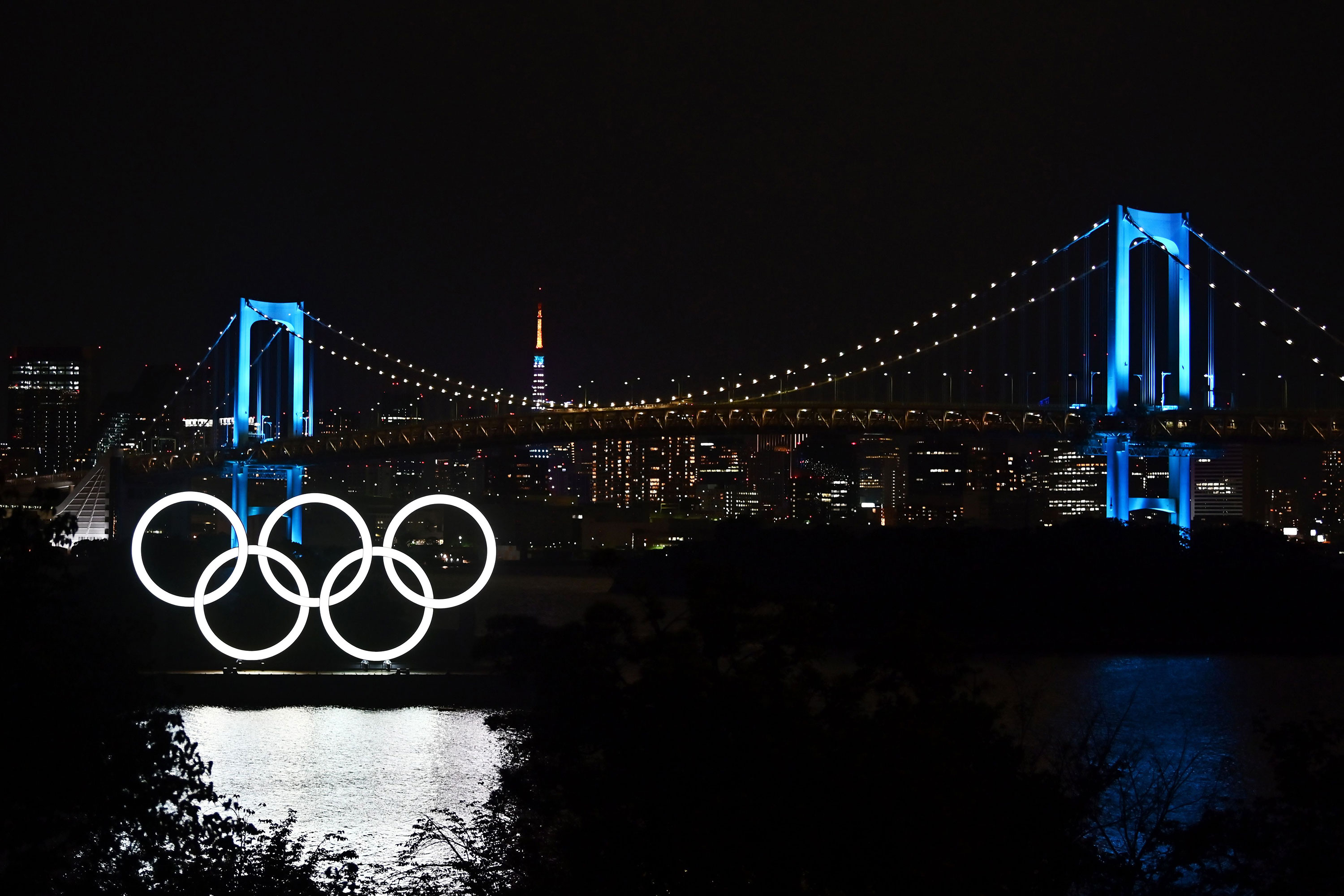 The Olympic rings, the Rainbow Bridge and the Tokyo Tower are seen at night in Tokyo on May 15.