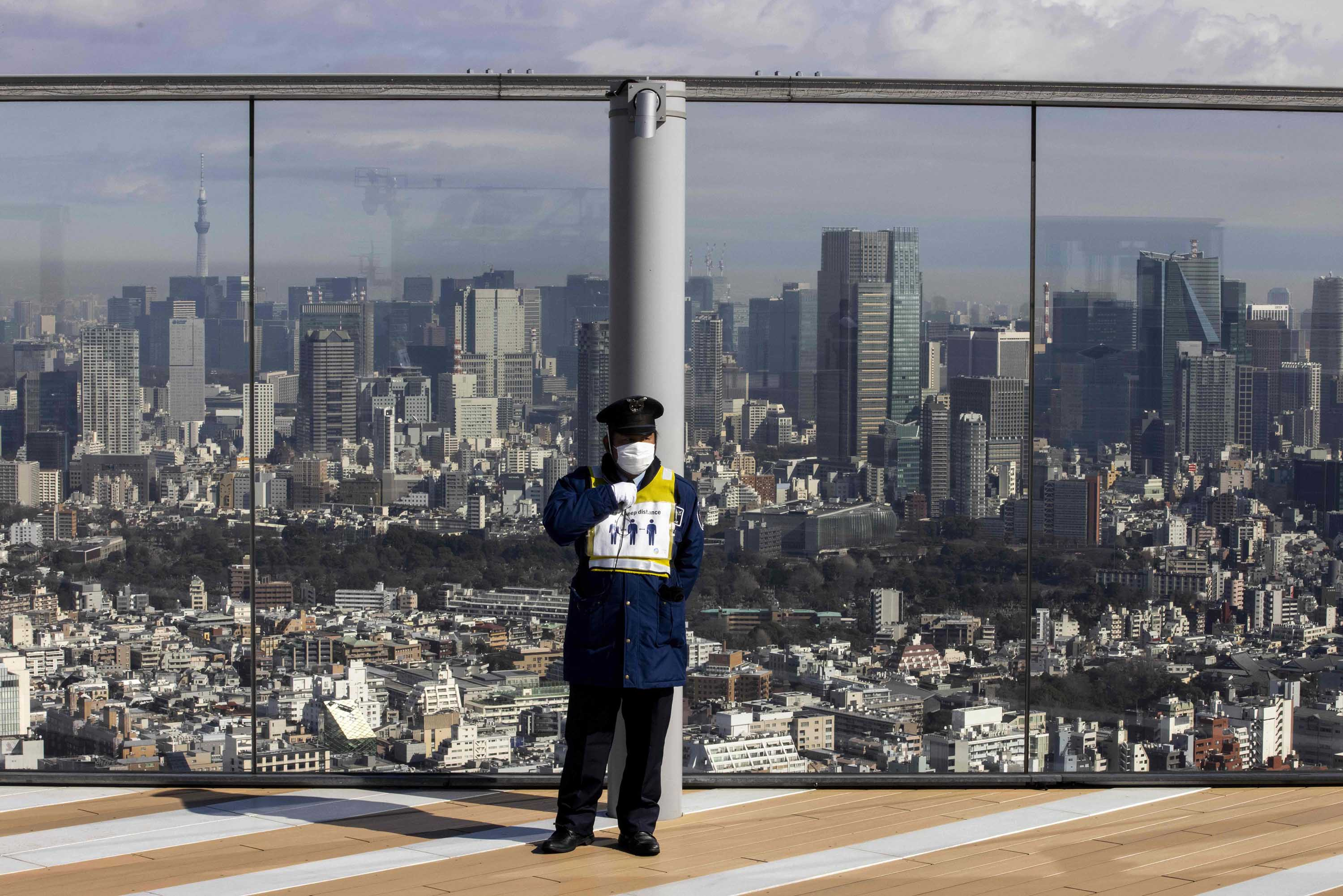 A security guard is seen on the Shibuya Sky observation deck overlooking Tokyo, on February 2, as Japan extended a coronavirus state of emergency in several parts of the country.