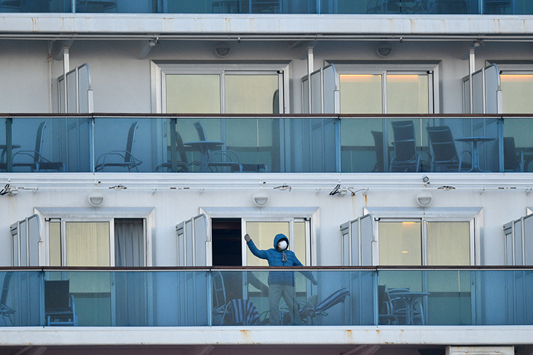 A passenger is seen on a balconies of the Diamond Princess cruise ship at the Daikaku Pier Cruise Terminal in Yokohama port onThursday, February 13.