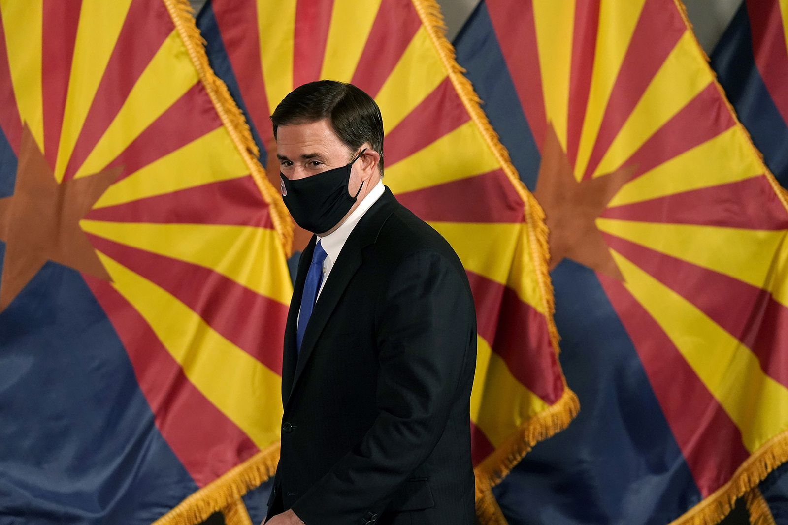 Arizona Republican Gov. Doug Ducey arrives for a news conference to talk about the latest Arizona V-19 information Wednesday, Dec. 2, 2020, in Phoenix. (AP Photo/Ross D. Franklin, Pool)