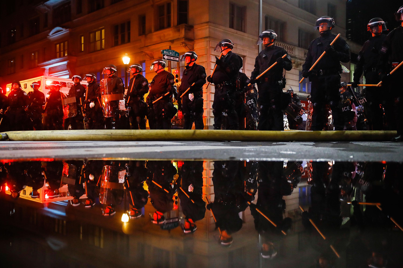 Police stand guard in Philadelphia on Saturday night.