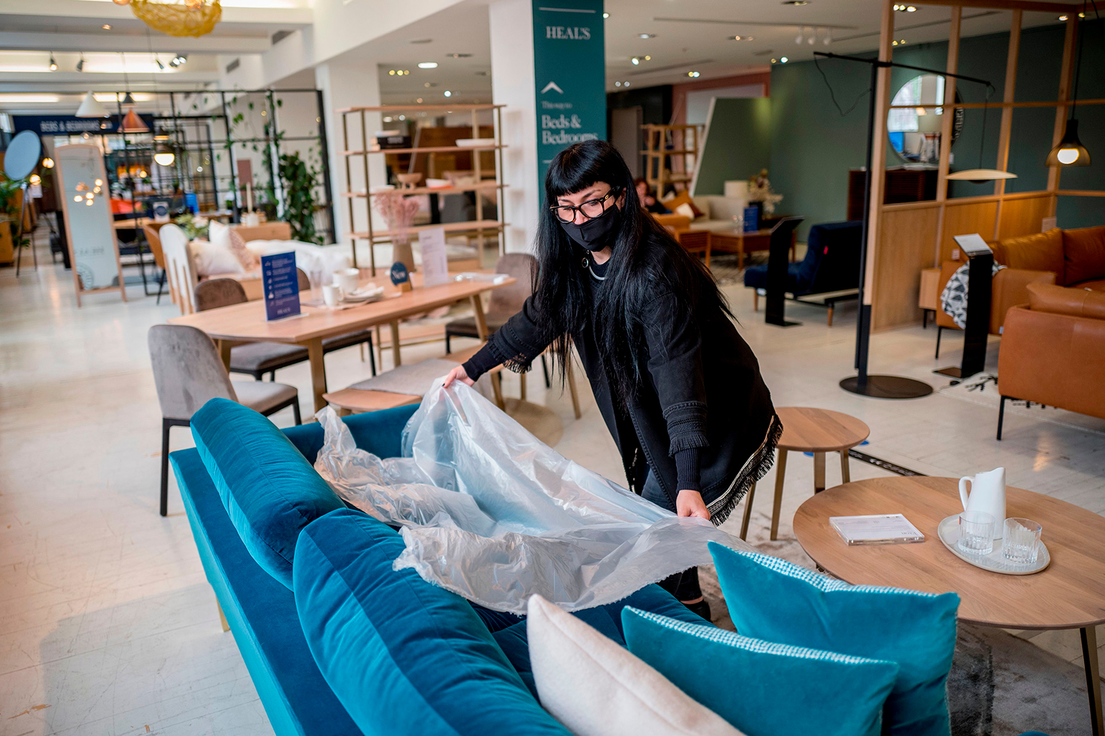 A woman demonstrates the use of plastic film for customers to test sofas, at the re-opened Heal's flagship store in central London on June 8.