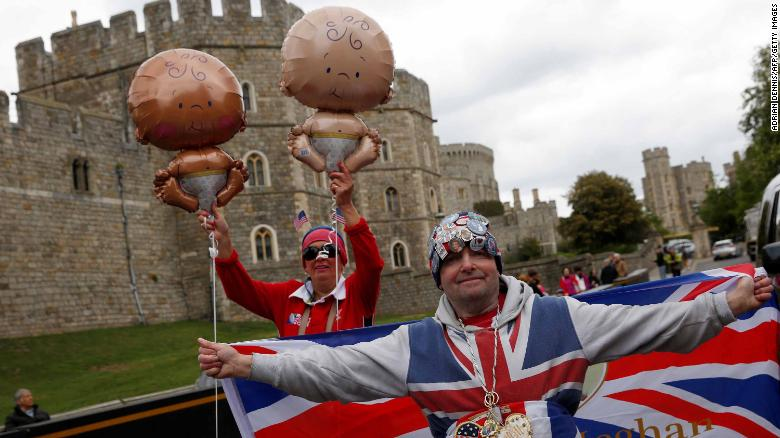Royal super fans John Loughery, right, and Anne Daley, left, hold onto baby-themed balloons outside Windsor Castle on Monday.