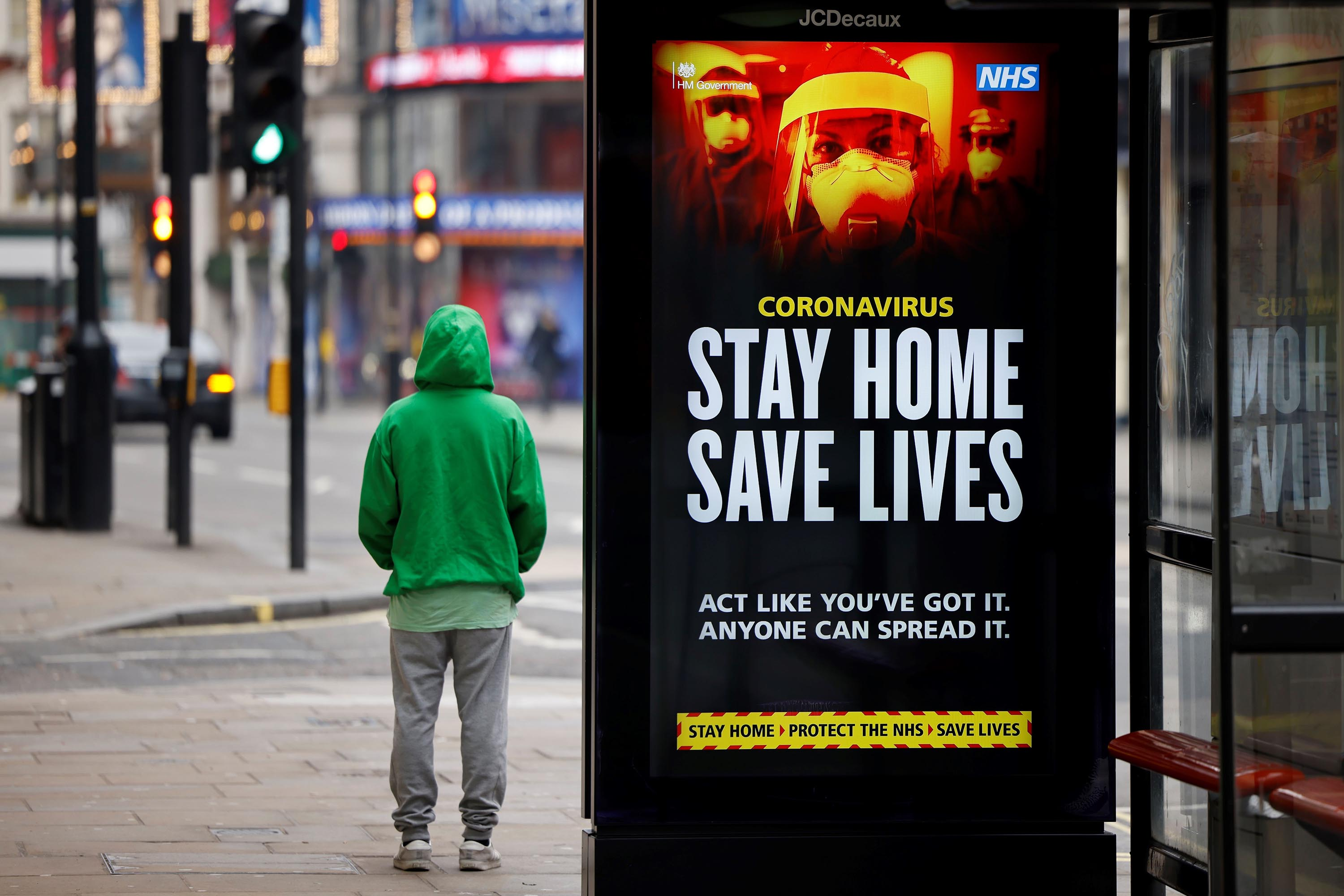 "A man stands near signage promoting the UK's National Health Service message, ""Stay Home, Save Lives"" on a bus shelter in London on January 8."
