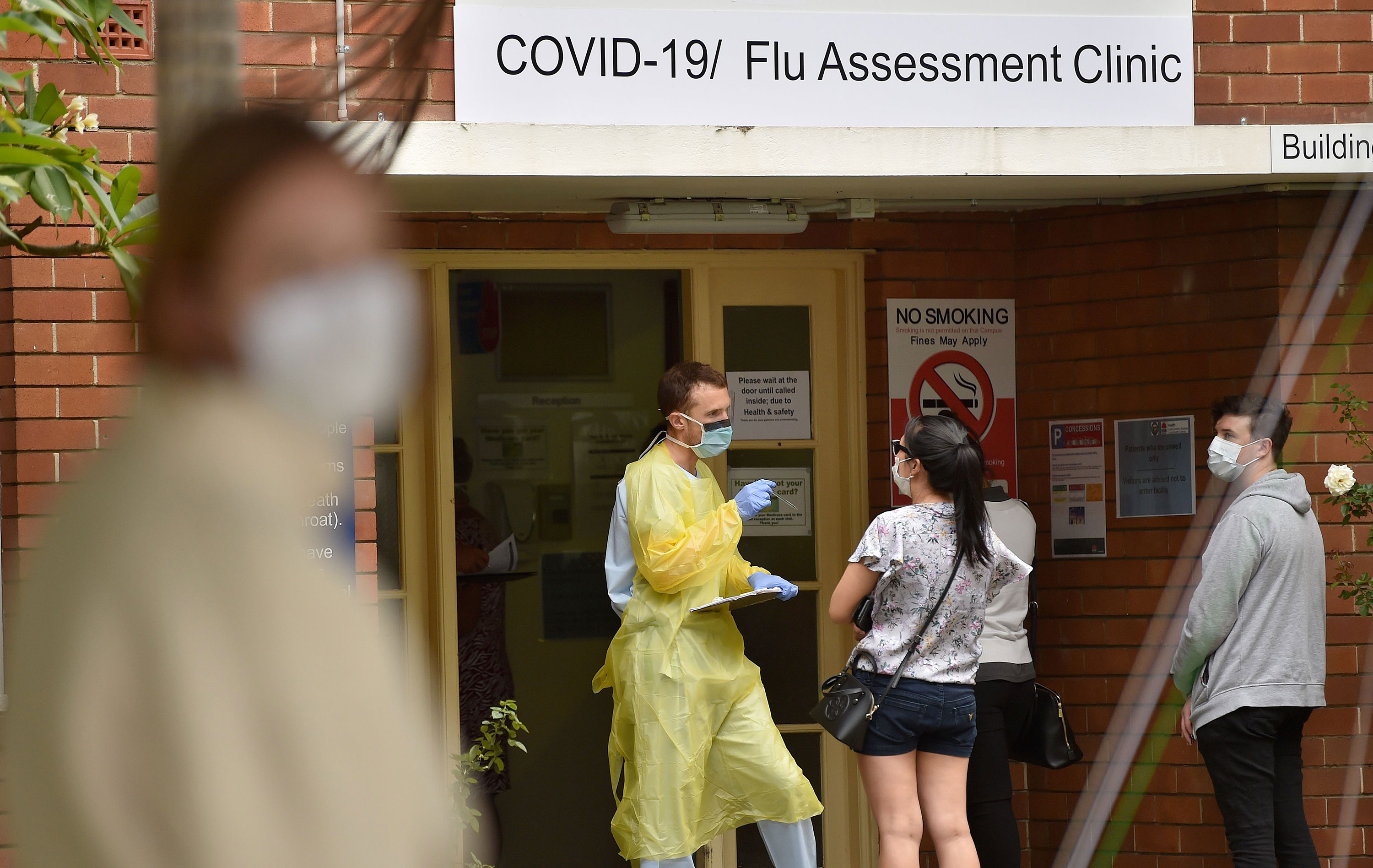 A health worker assists visitors at a coronavirus testing center in Sydney on March 23.