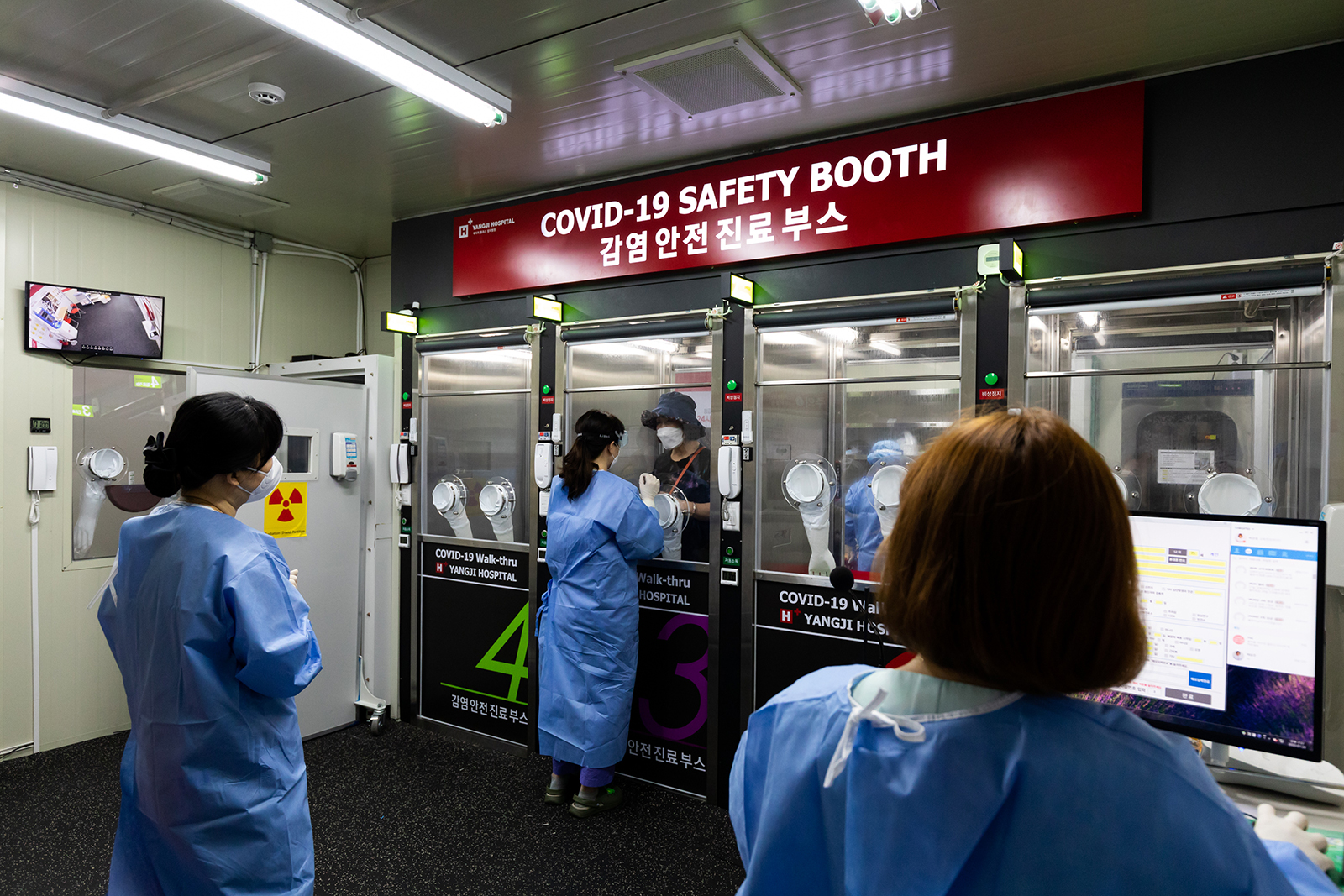 A medical worker wearing personal protective equipment (PPE), center, speaks with a visitor from inside the Covid-19 safety booth in the walk-thru testing center at H Plus Yangji Hospital in Seoul, South Korea, on July 24.
