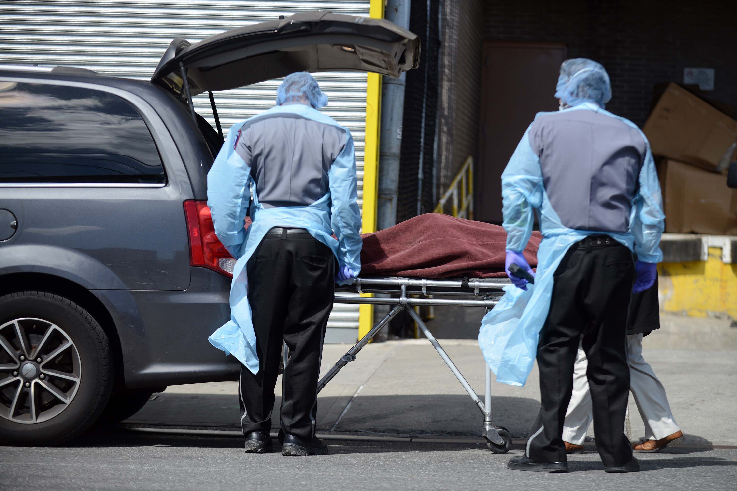 A deceased coronavirus patient is loaded into a waiting funeral home van outside Wyckoff Heights hospital in Brooklyn, New York, on April 2.