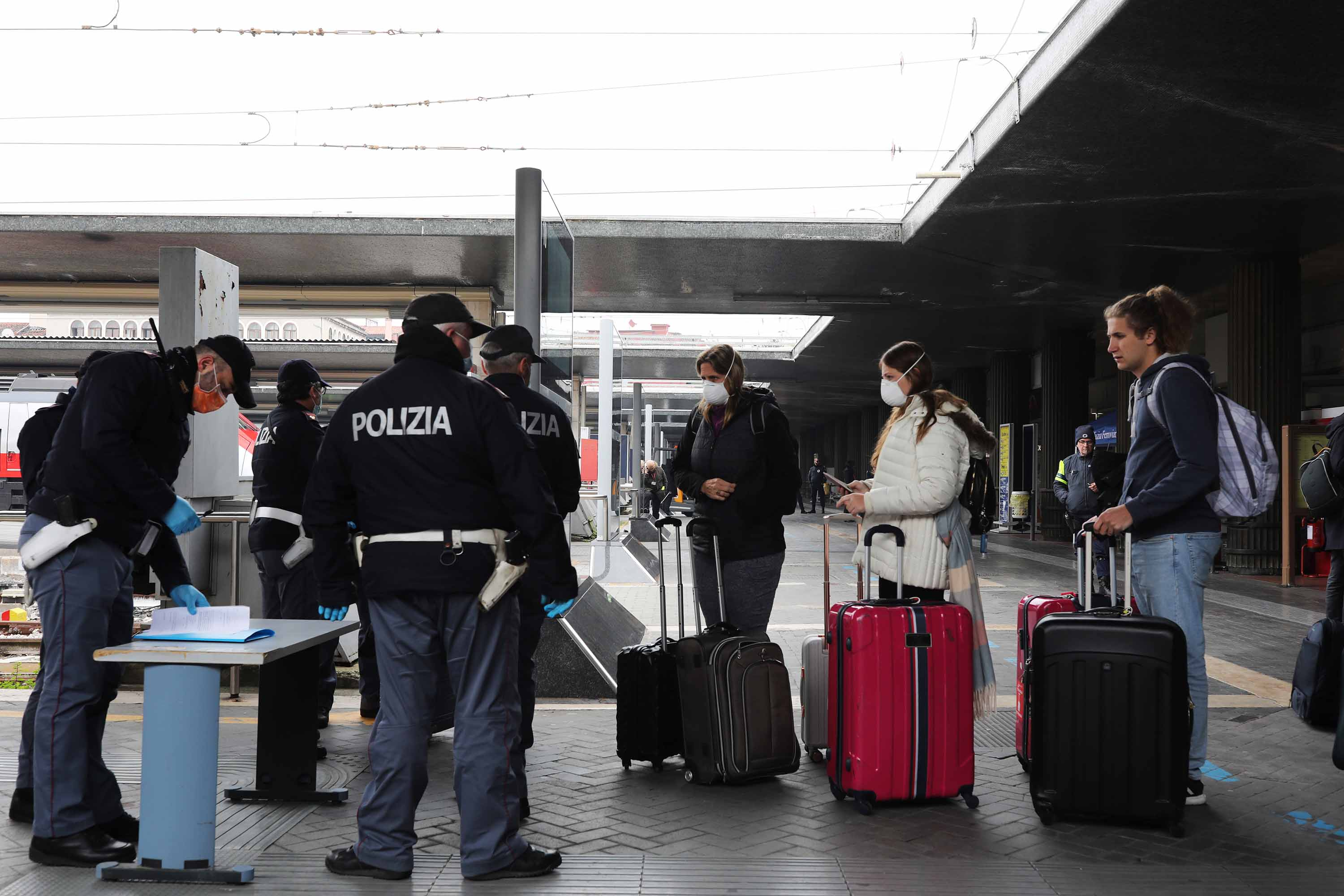 Police officers check travelers at the Venice Santa Lucia railway station on Tuesday.