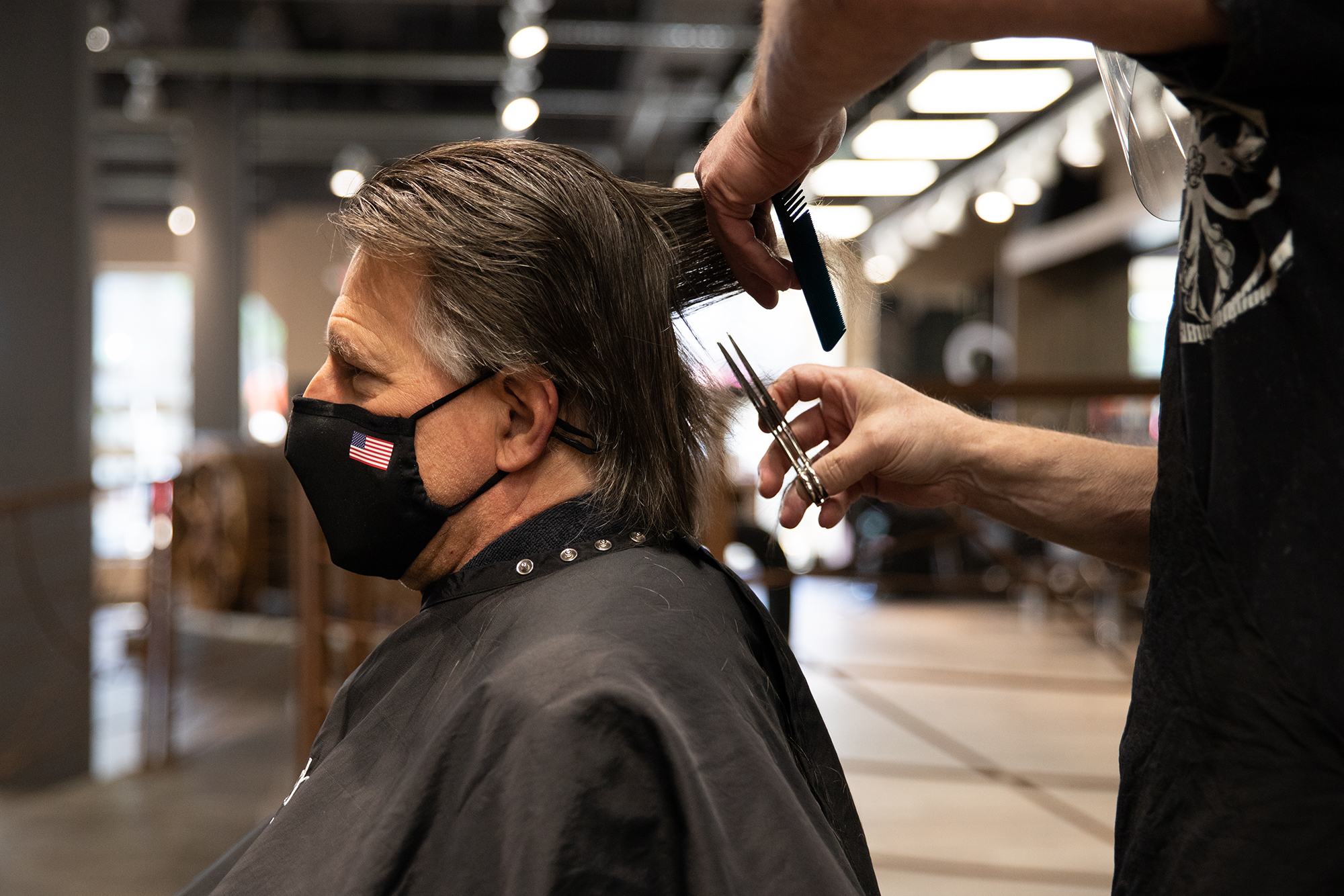A customer wearing a protective mask receives a haircut at a salon in Royal Oak, Michigan, on June 15, 2020.