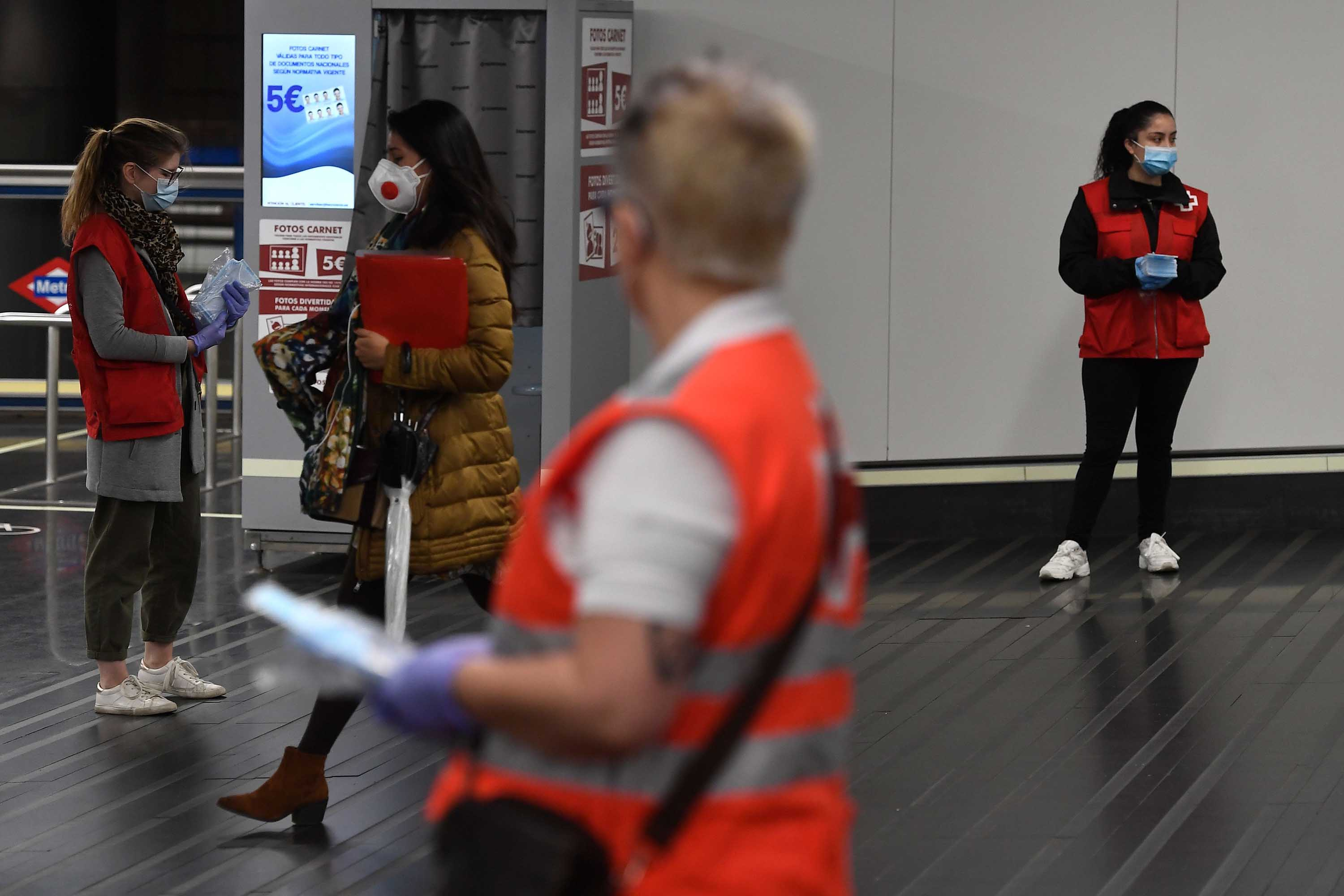Spanish Red Cross volunteers distribute face masks at the Chamartin Station in Madrid on April 13. Some companies are set to resume operations after the government lifted some of the country's lockdown restrictions.