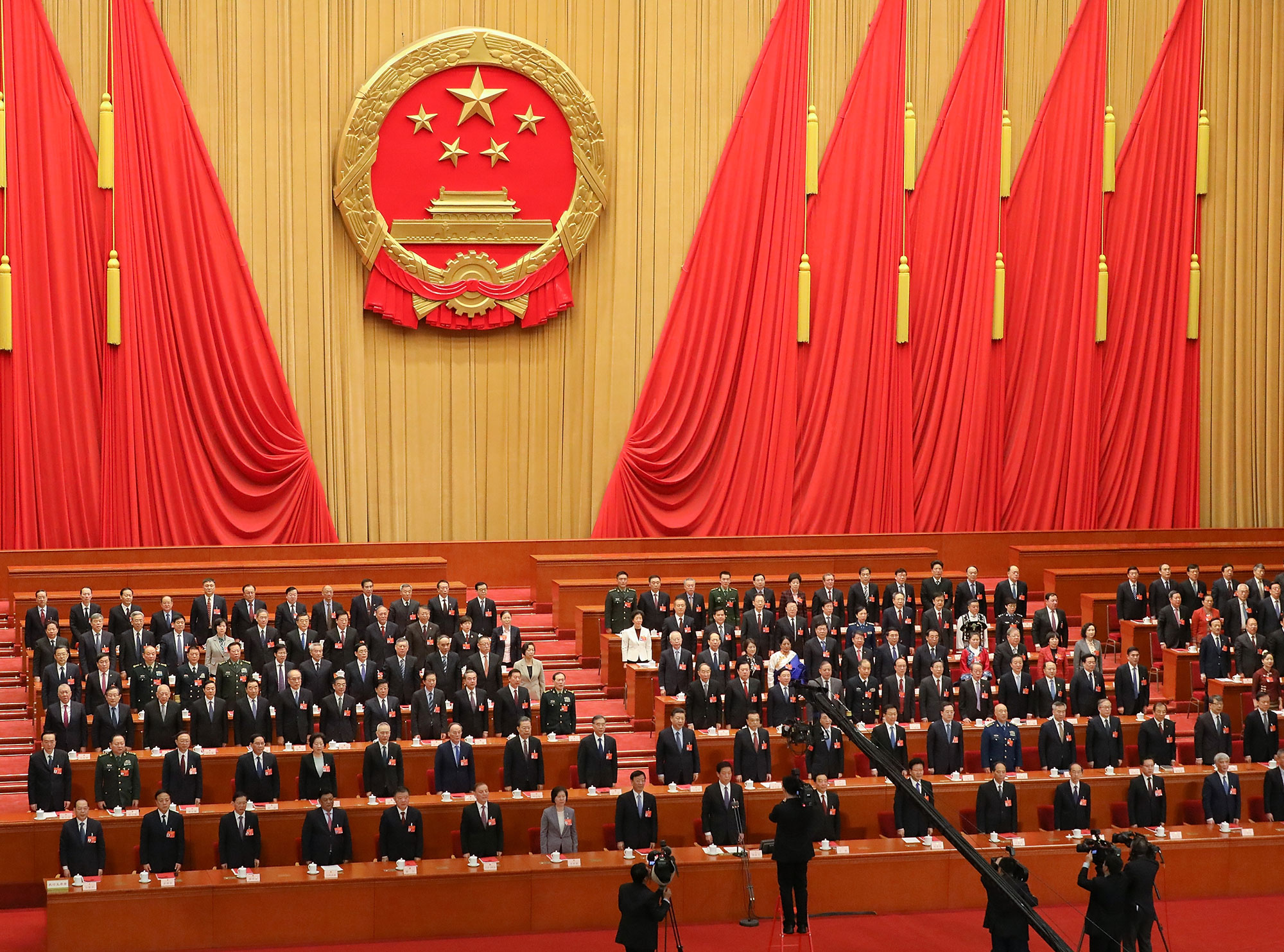 Chinese President Xi Jinping and the other attendees of the fourth and last Plenary Meeting of the National People's Congress stand and listen to the National Anthem at The Great Hall Of The People on March 15, 2019 in Beijing.