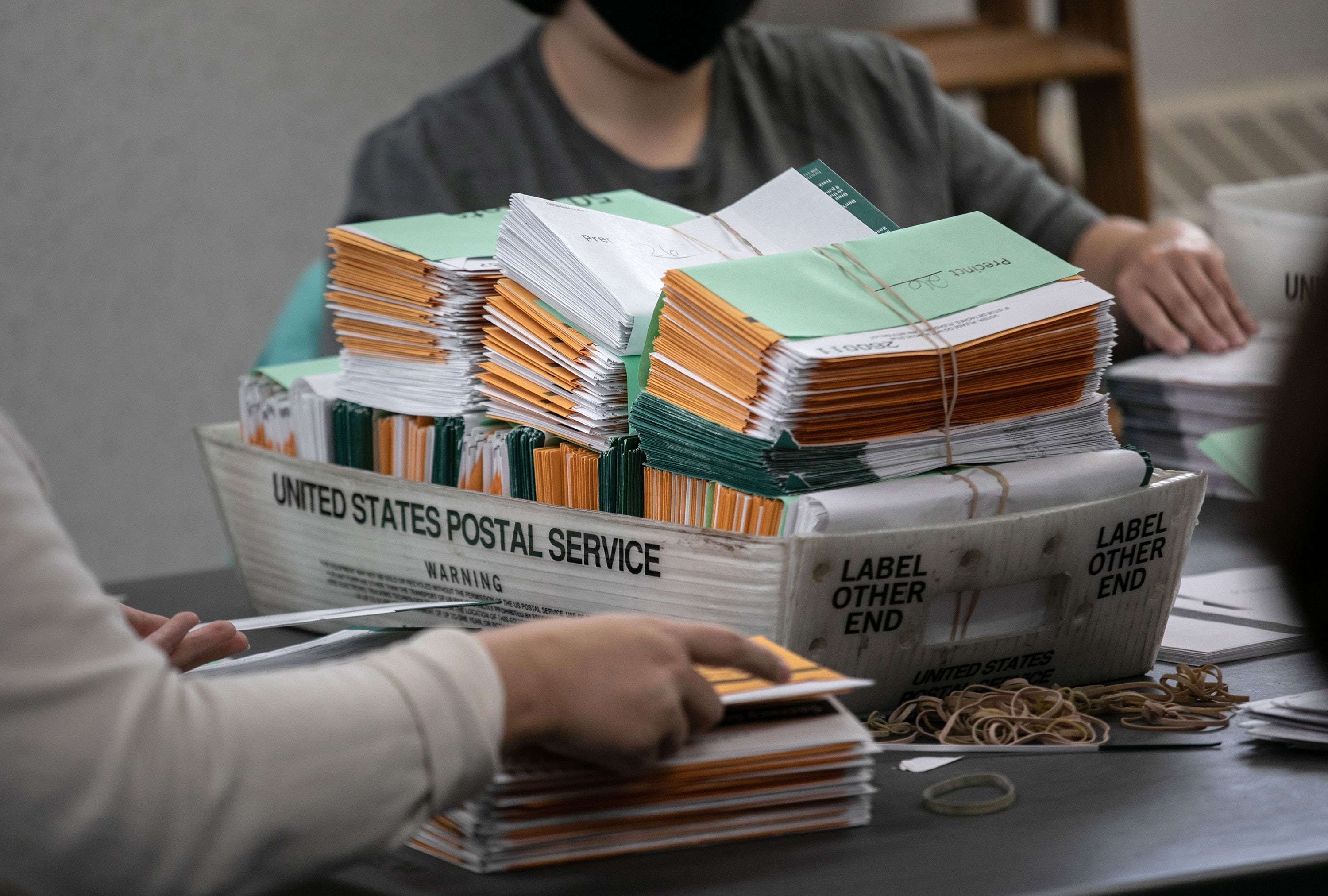 Election workers sort absentee ballot envelopes at the Lansing City Clerk's office on November 2 in Lansing, Michigan.