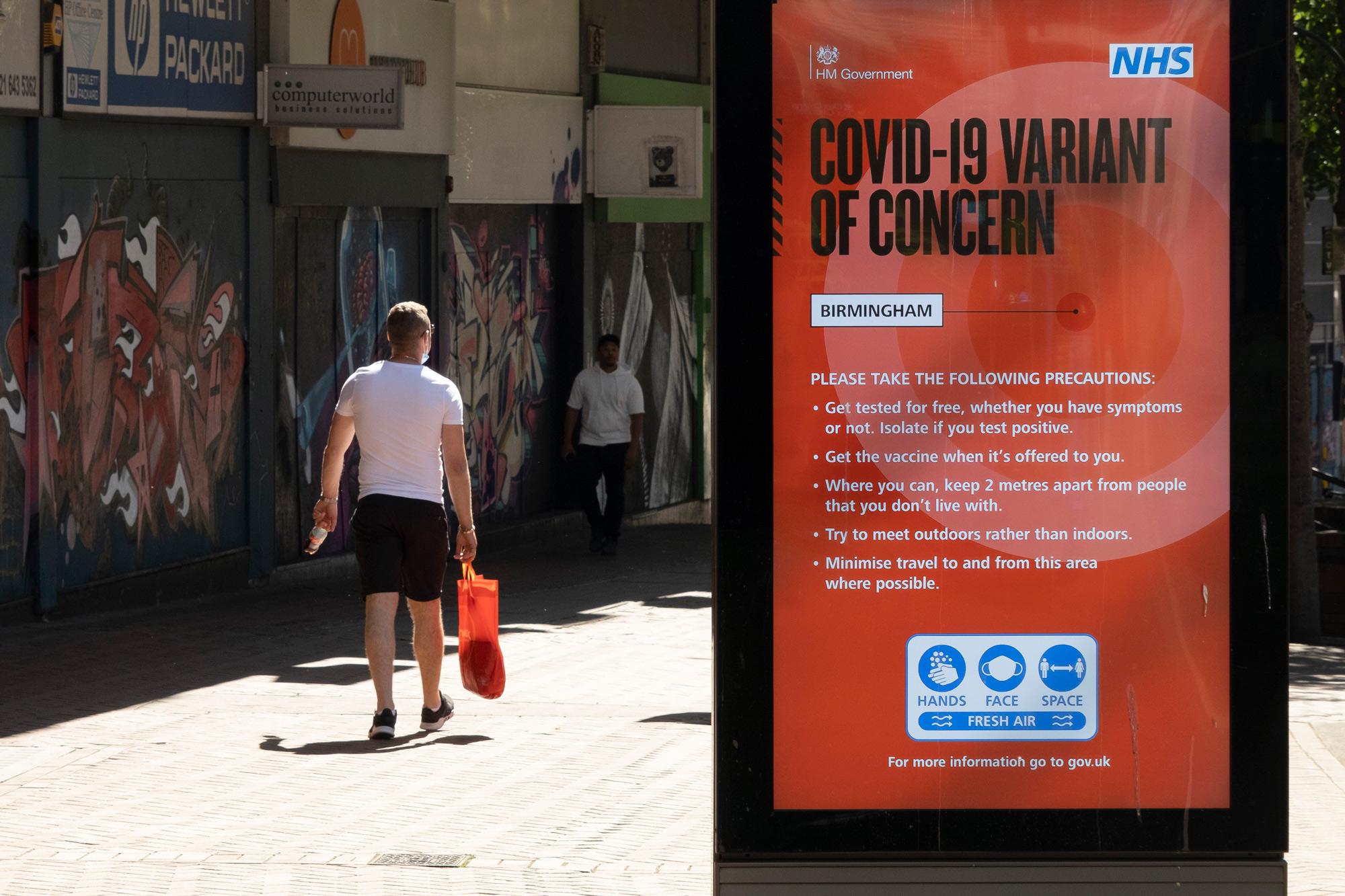 People walk by a sign on June 15 in Birmingham, United Kingdom.