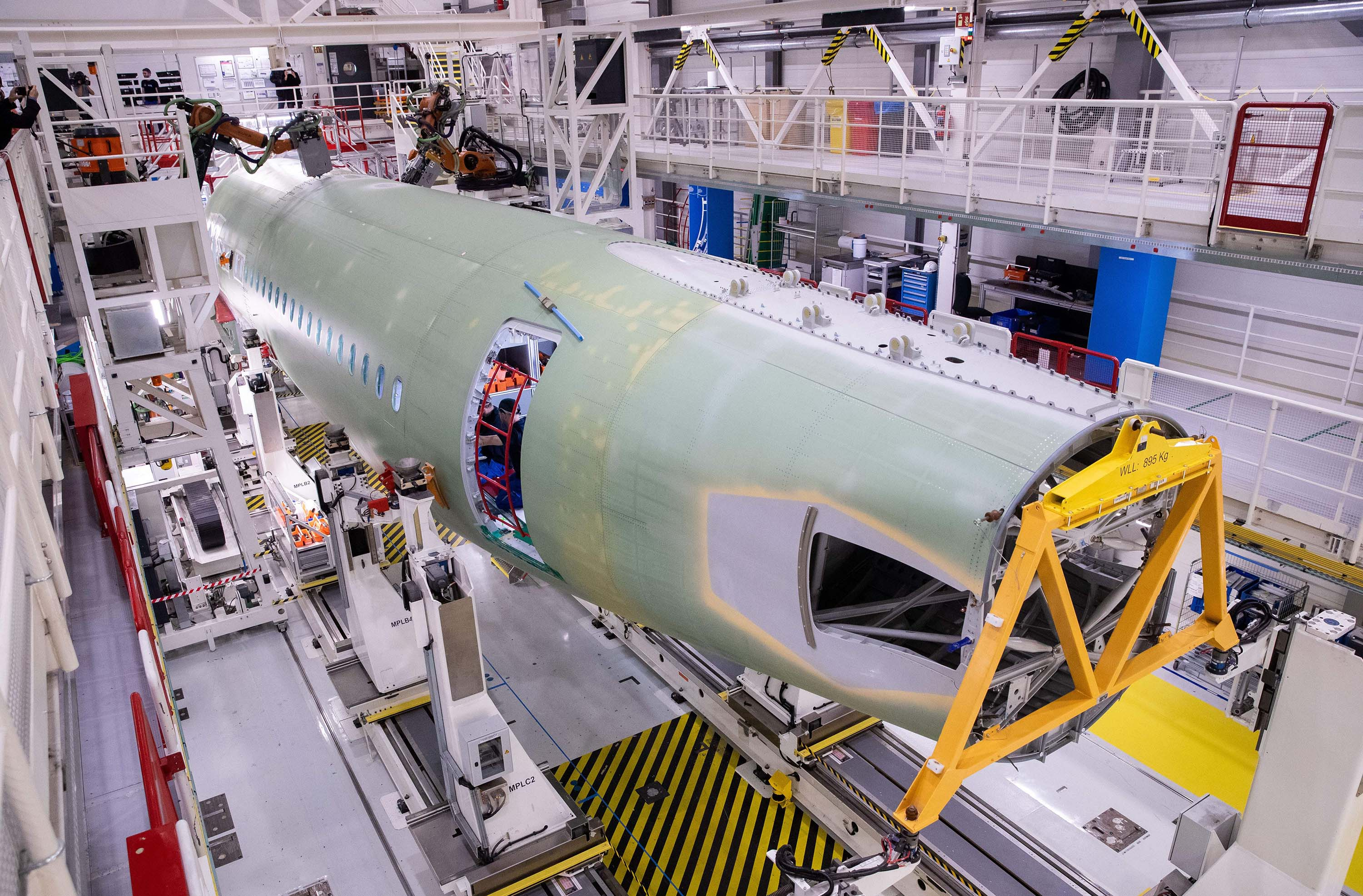 Airbus technicians work on parts for an Airbus A320 at the company's Finkenwerder plant in Hamburg, Germany, in October 2019.