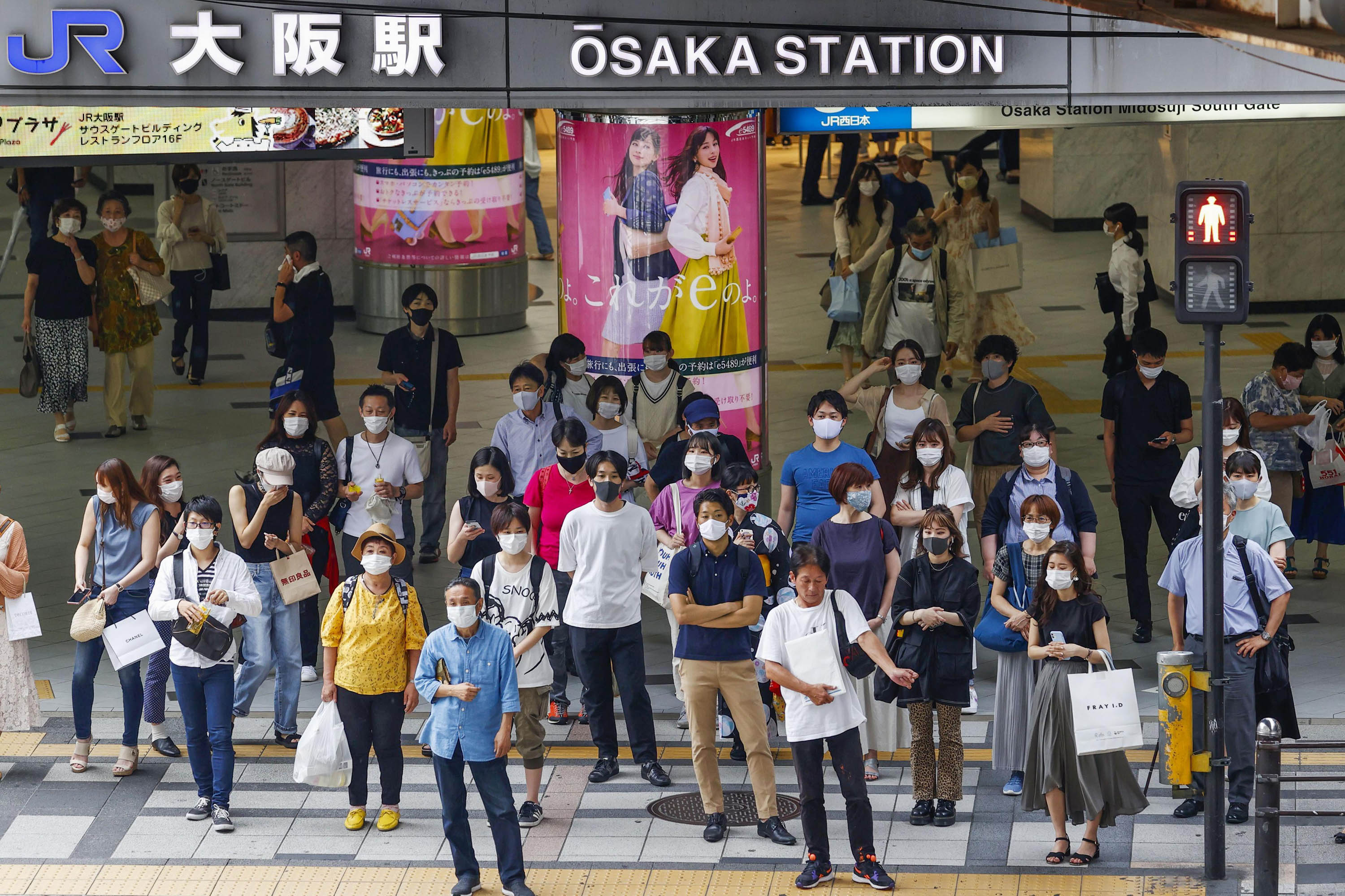 People wearing face masks are seen in front of Osaka Station on July 22, amid the spread of the novel coronavirus.