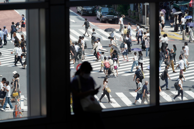 People walk across a busy crossing in Tokyo on July 24.