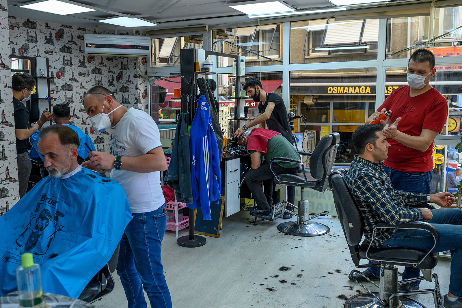 Barbers cut hair while wearing protective face masks in a barber shop in Istanbul on May 11.